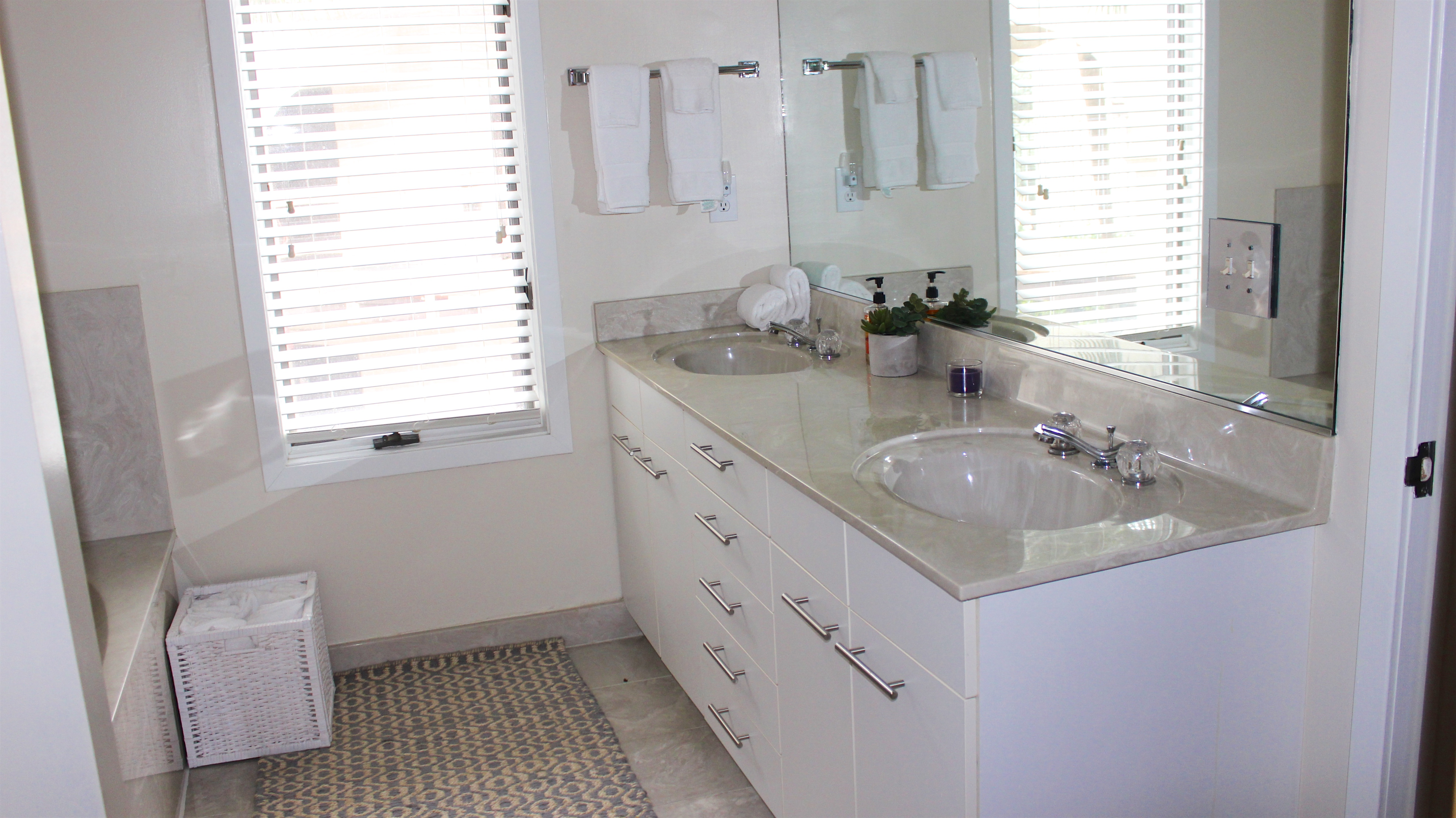 The master bath has a vanity with a double sink and stone counter.
