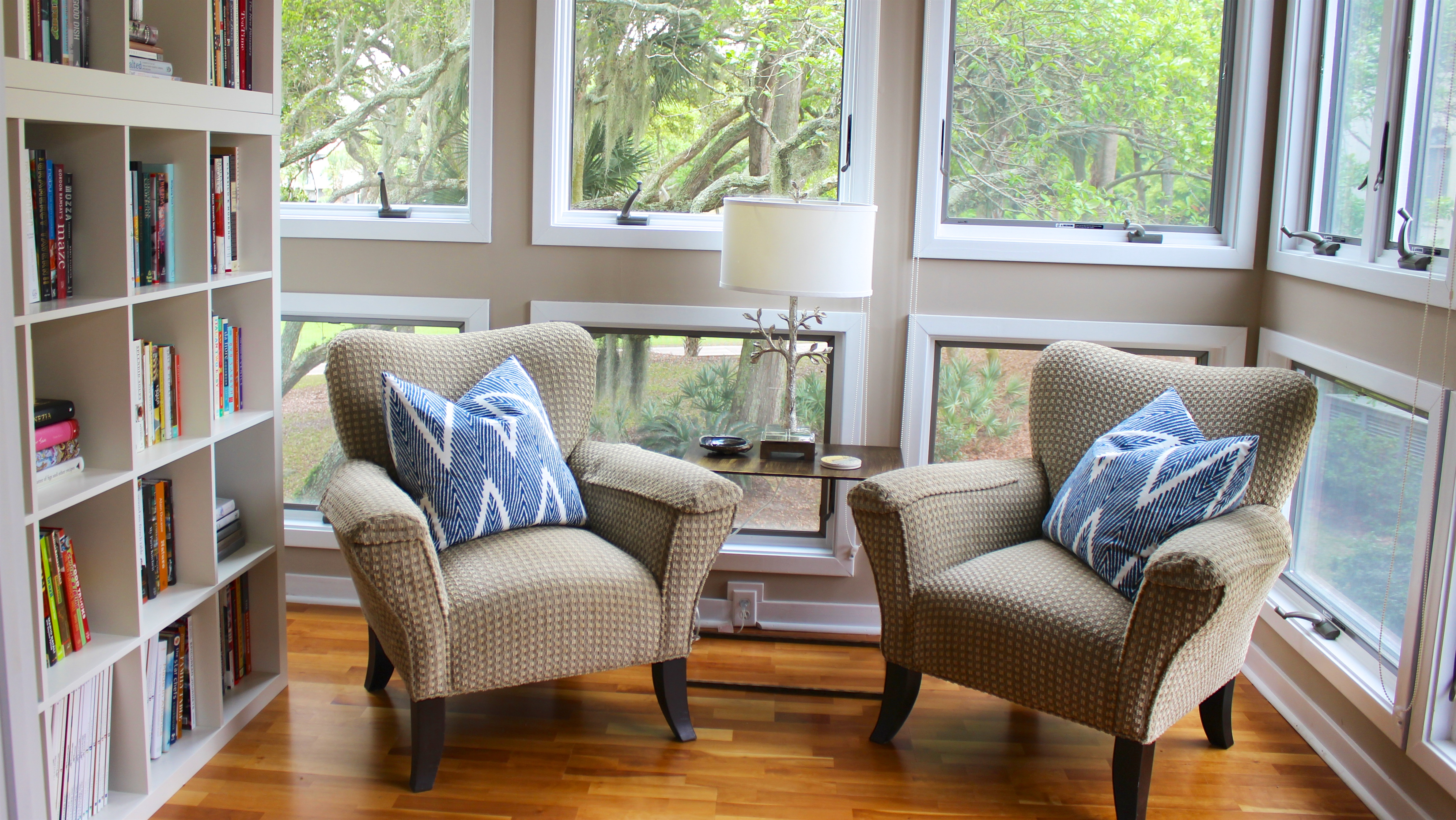 The sunroom has been cleverly divided and has comfortable chairs and book shelves.