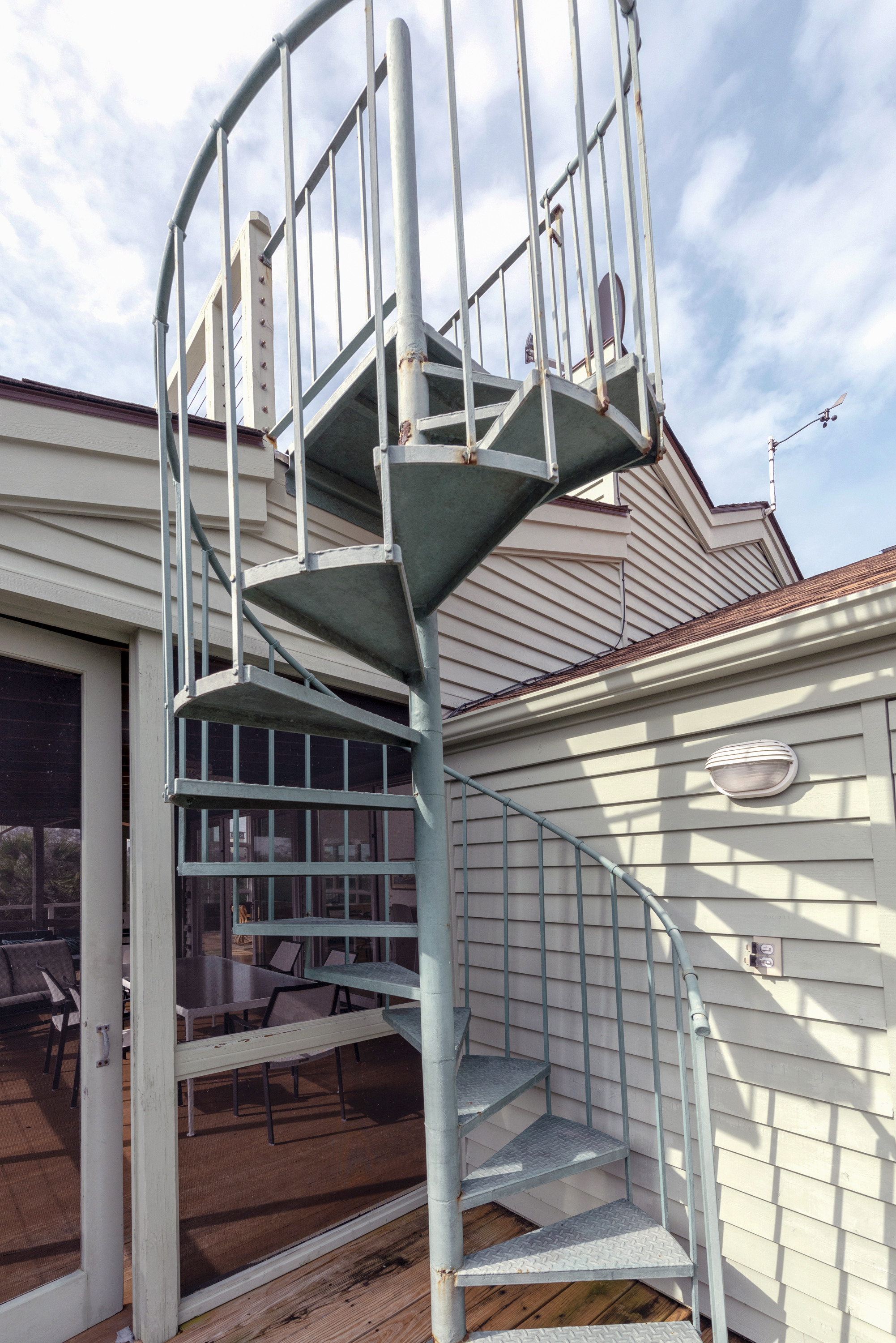 Spiral stair outside of screened porch to roof deck