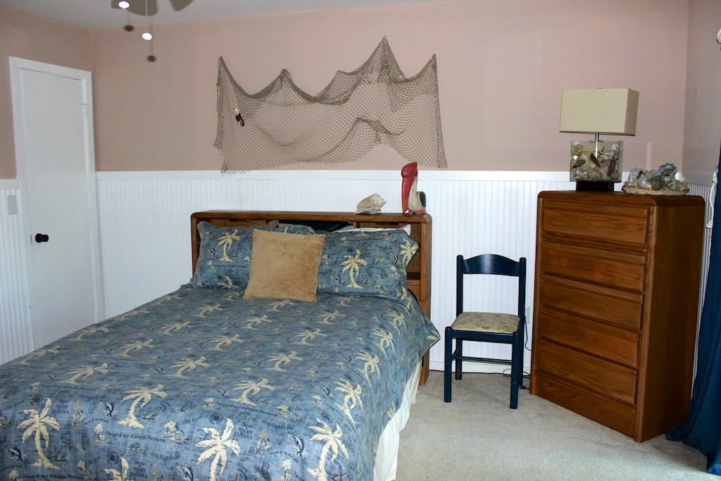 The 2nd bedroom has a queen bed and tropical decor.