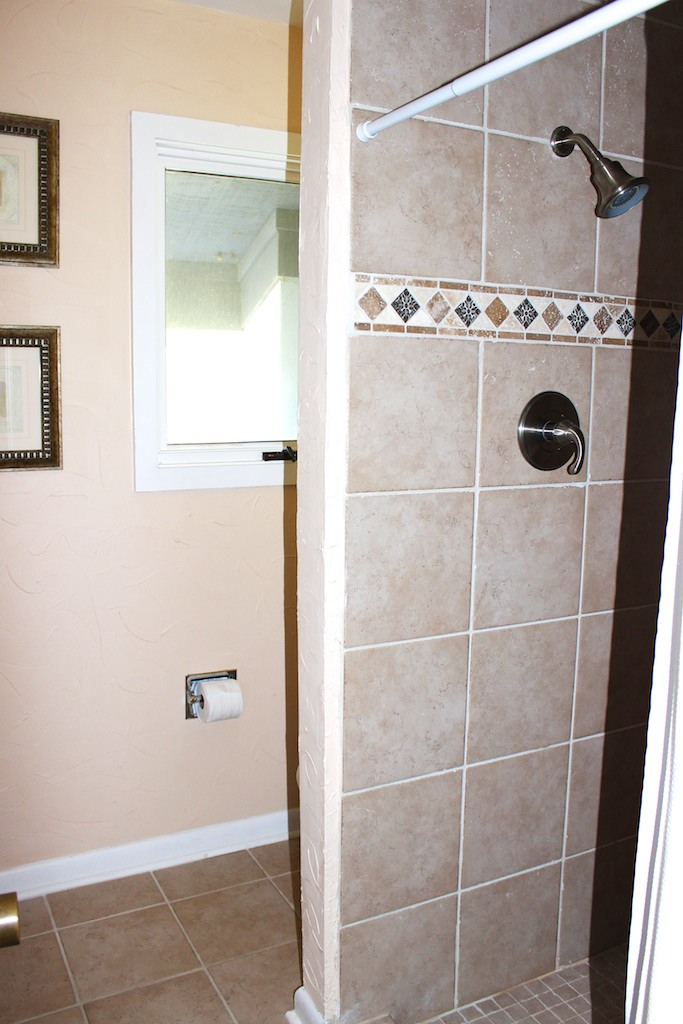 It has a tiled shower and separate toilet area.