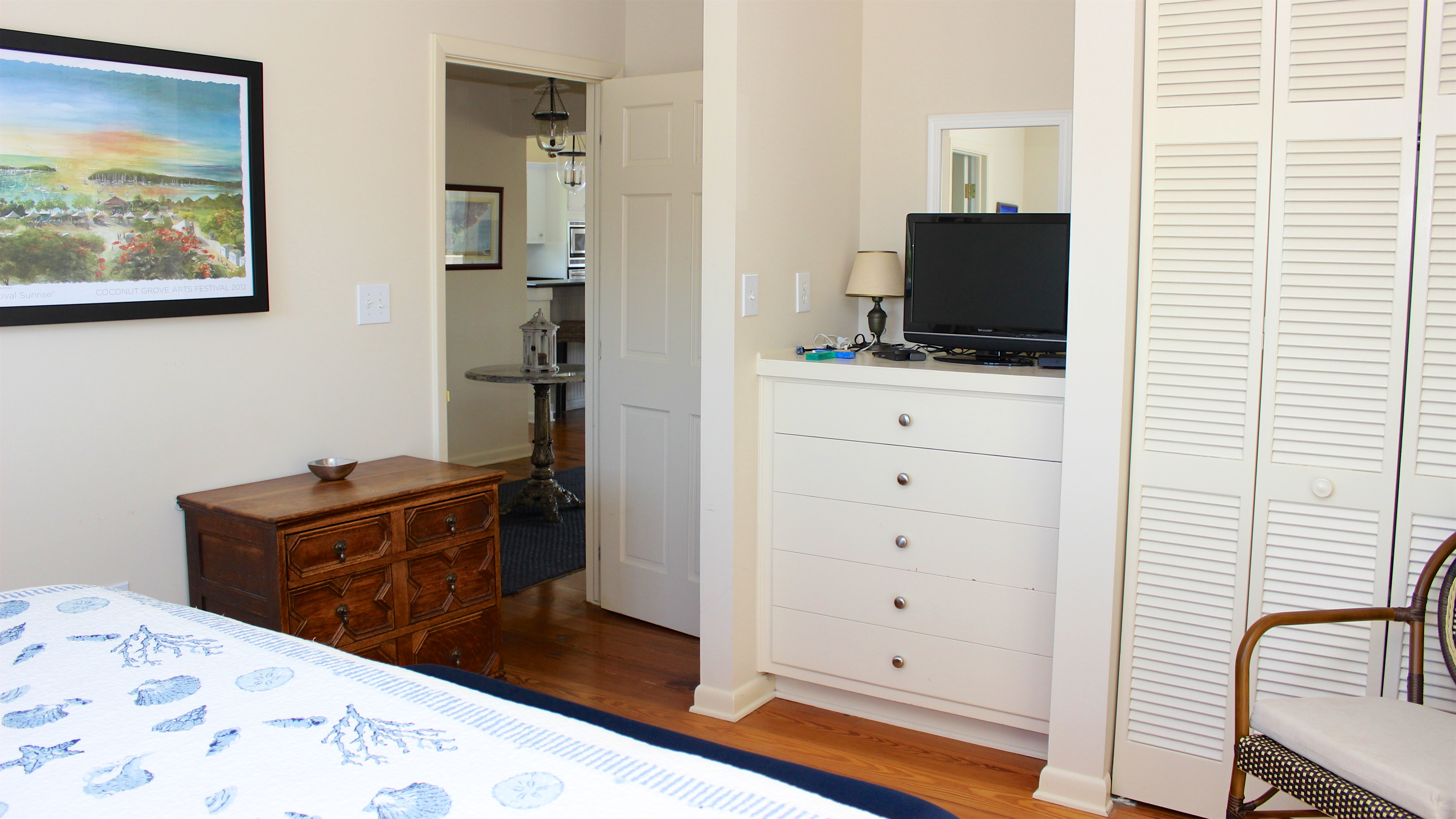 A TV sits atop the built in dresser. There is an en suite bathroom.