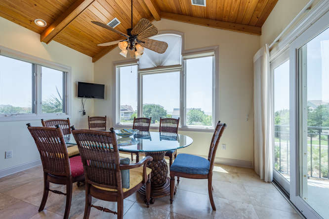 The dining area in the kitchen has oceanview, sliding doors leading to the front deck and even a mounted TV!
