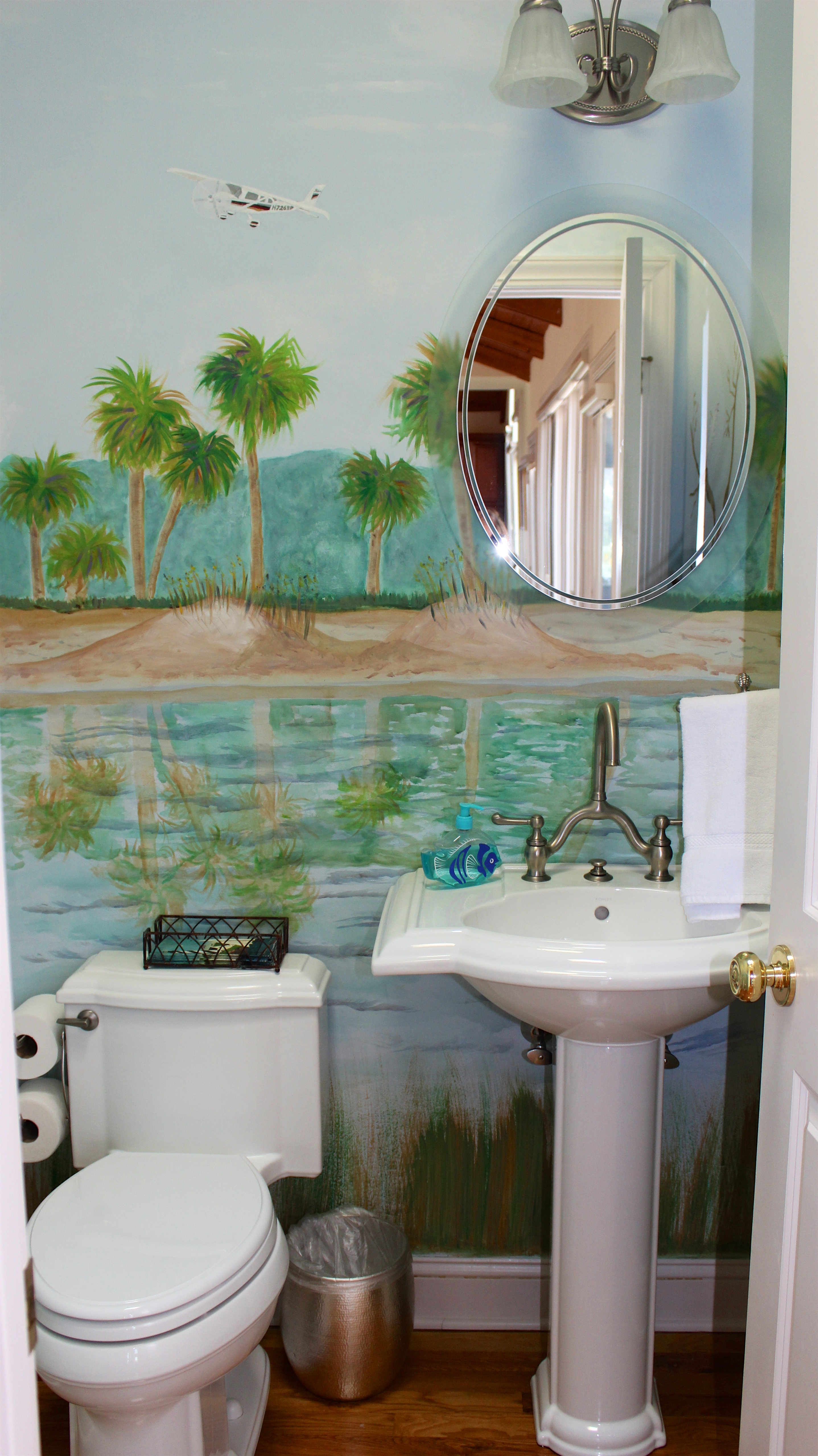A hand-painted low country landscape is featured in the powder room.