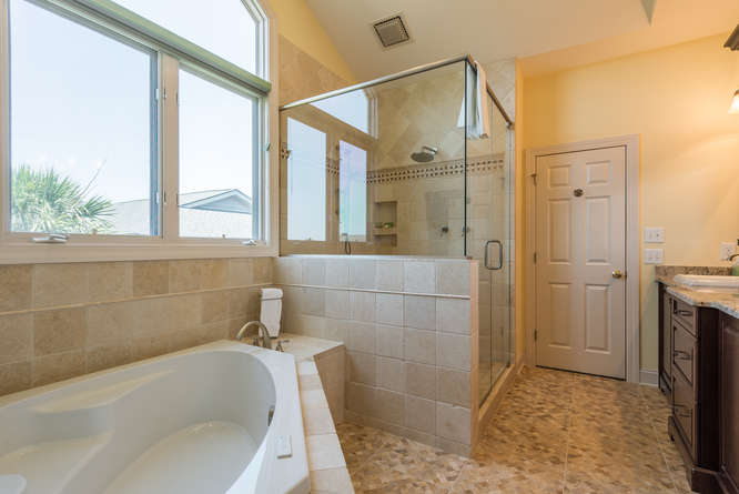 The master bath has a large tiled shower with rain head, jacuzzi tub with TV overlooking it.