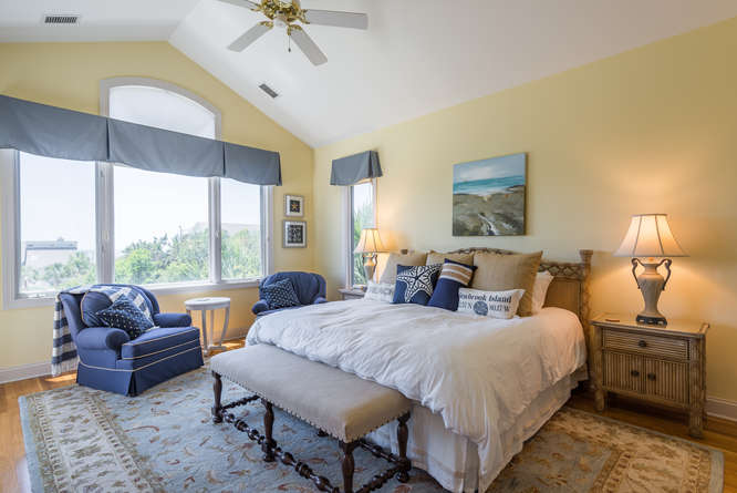 The master bedroom has a king bed, seating, & ocean views.