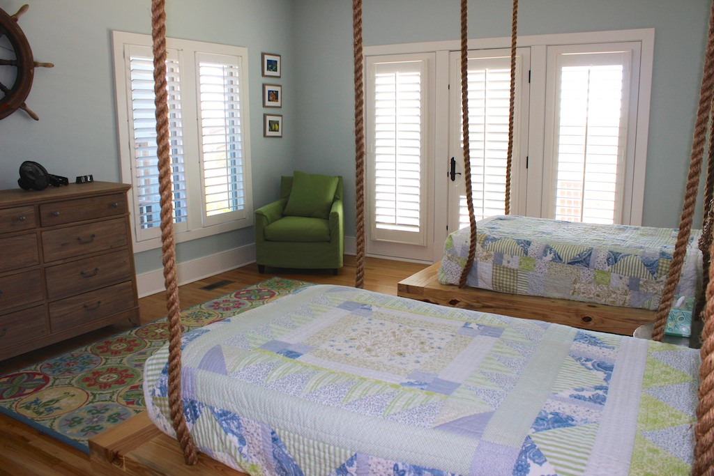 The 4th bedroom has two twin beds with ship ropes creating a unique bed frame.