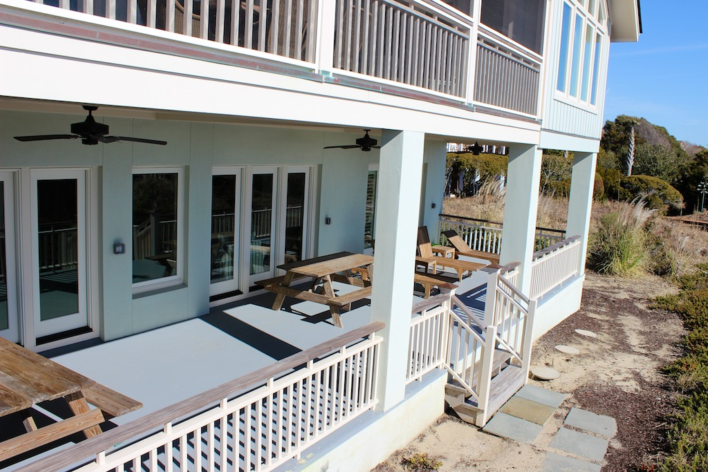 Steps lead to the beach path from the screened porch and patio below.