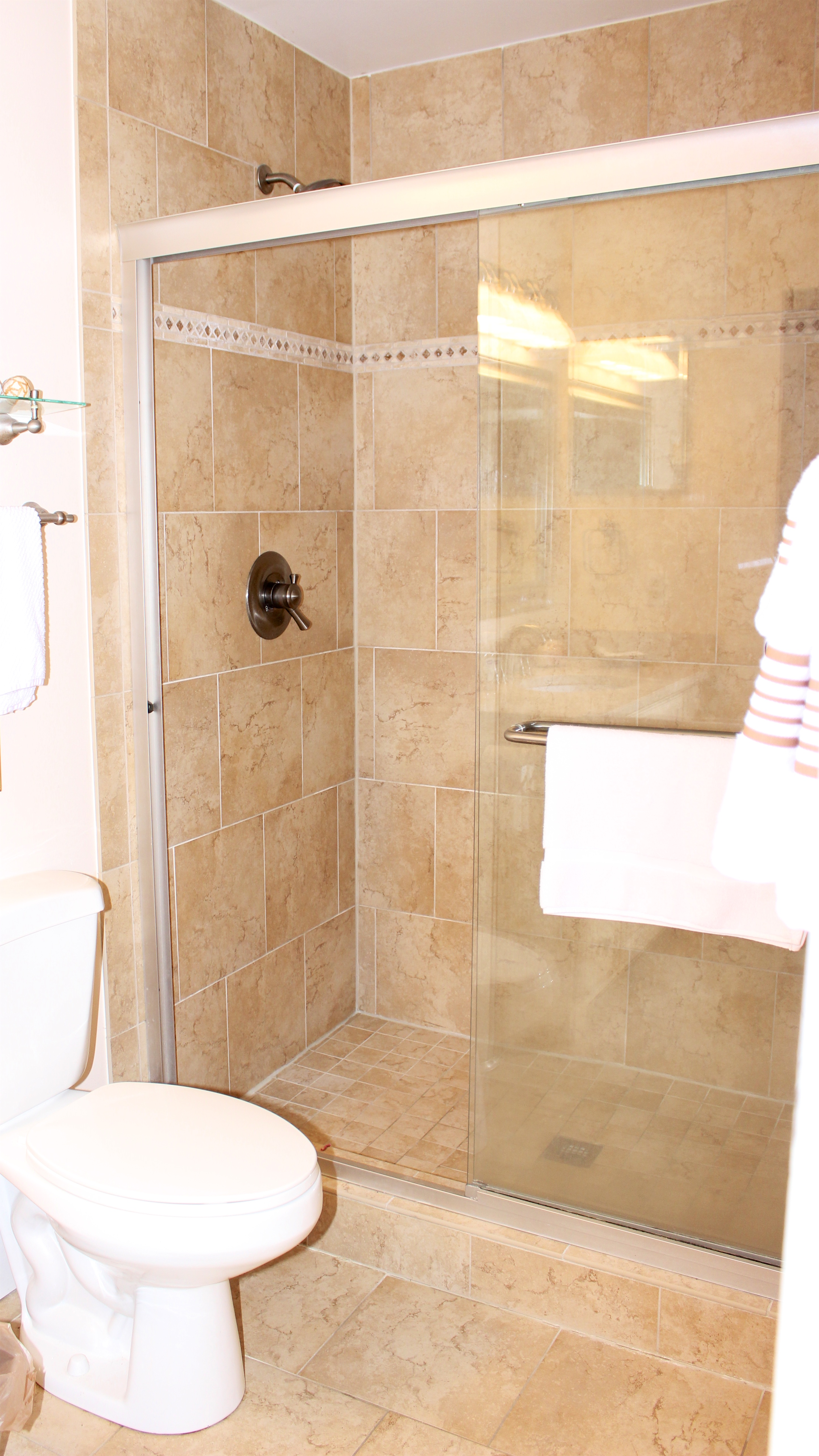There is a large tiled shower with a glass door.