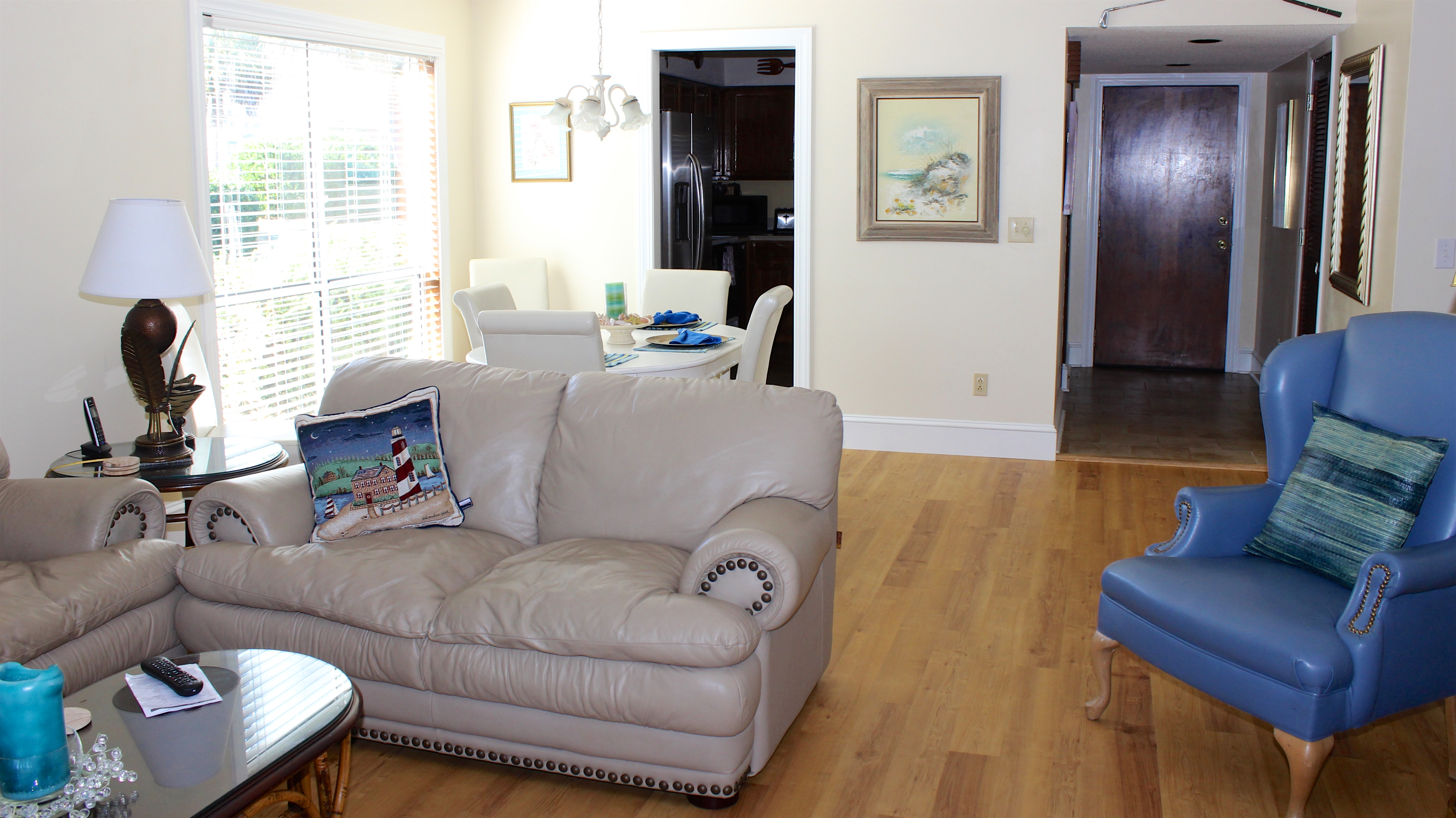 The open living area has high ceilings. The kitchen and dining area are nearby.