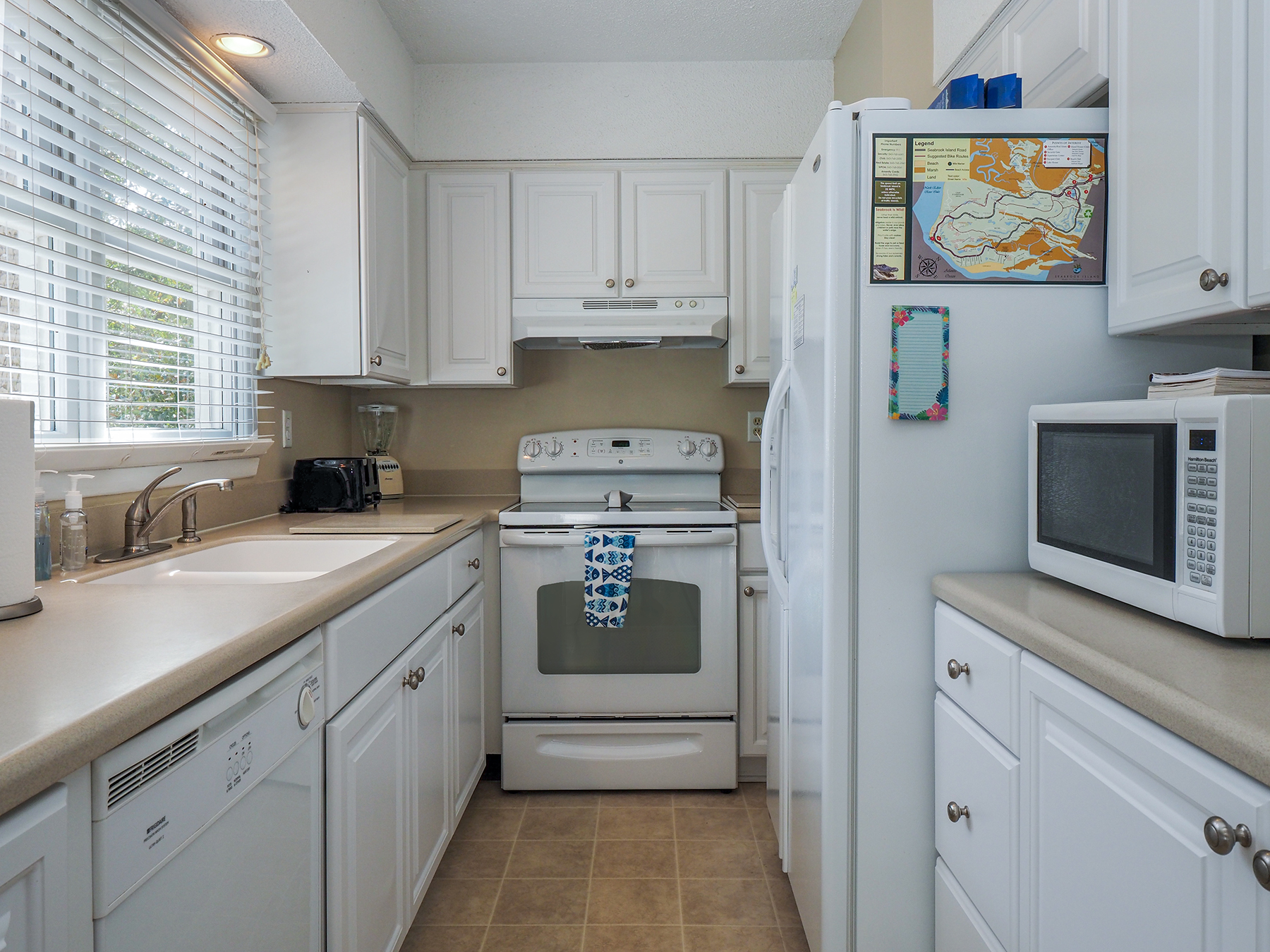 Galley kitchen with natural light from window above sink