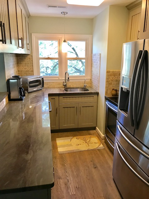 The galley kitchen features granite counter tops and stainless steel appliances.