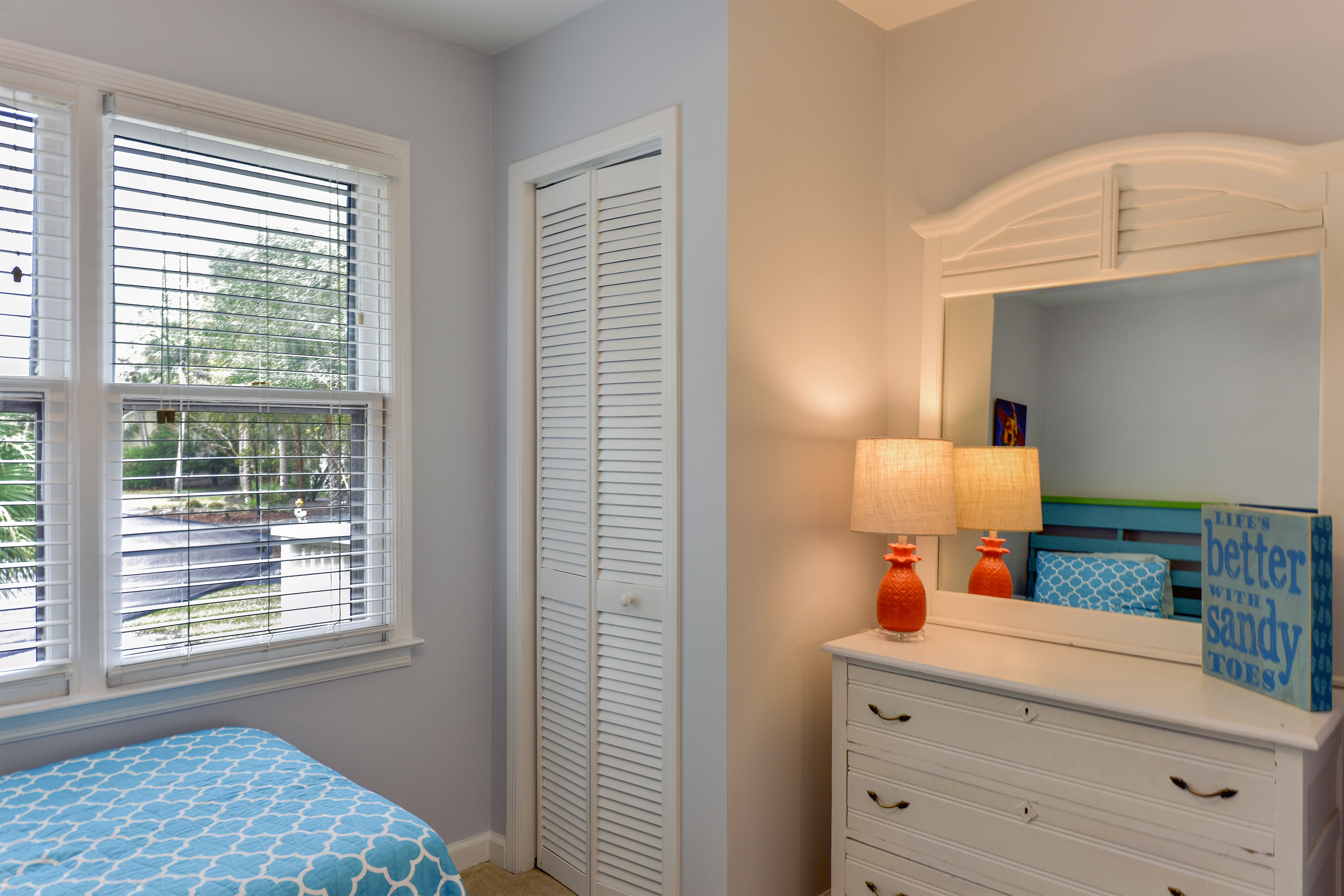 The twin guest bedroom has a dresser and closet.