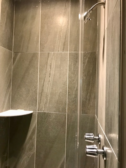 The master bathroom shower is beautifully tiled and has a seamless glass shower door.