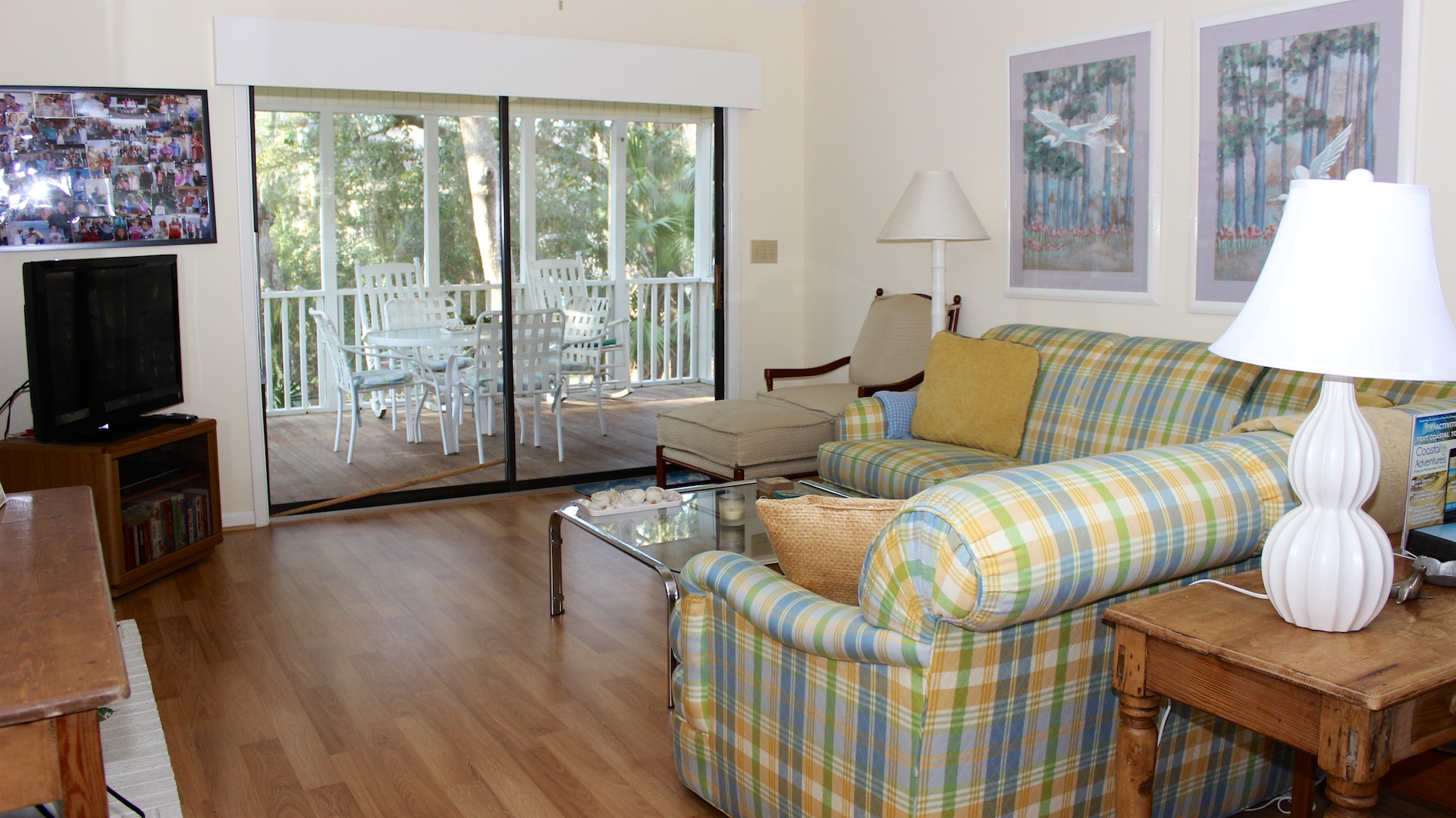 The sliding doors to the screened porch allow sunlight to filter through the trees.