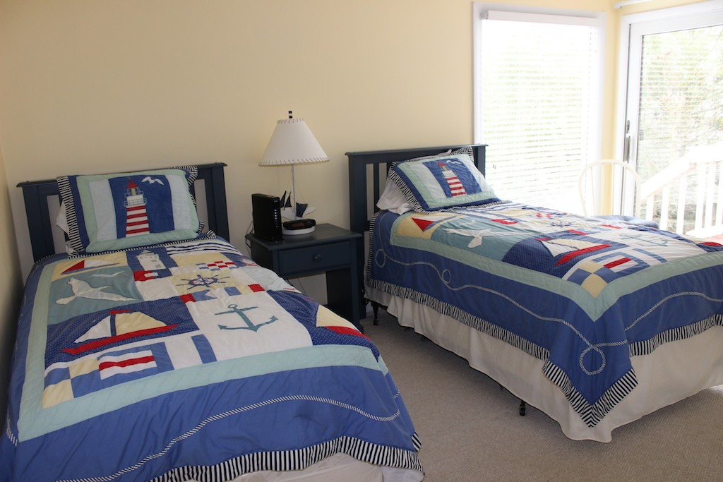 This 1st floor bedroom has two twin beds and a nautical decor. Sliding doors open to the deck