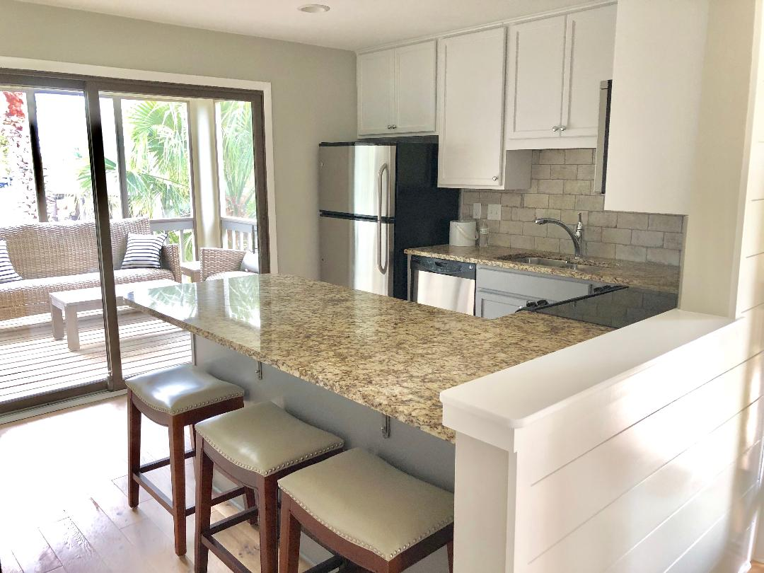 Open floor plan in kitchen with sliding doors leading to screened in porch.