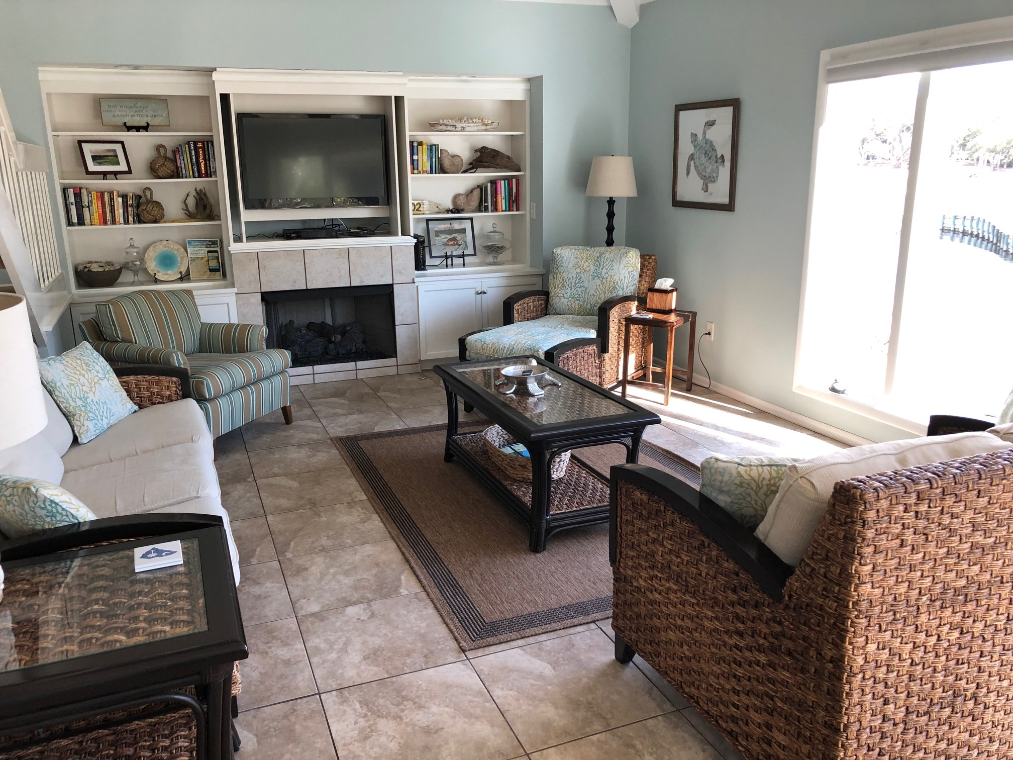 The town home features tile flooring and  bookshelves with an HDTV.