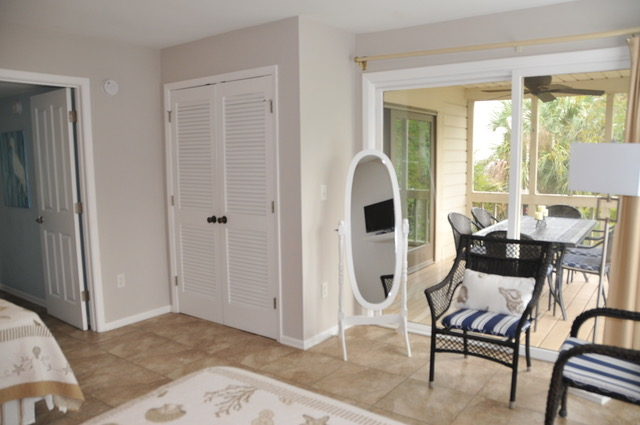 Watch shows on the wall mounted TV. Doors lead to the screened porch.