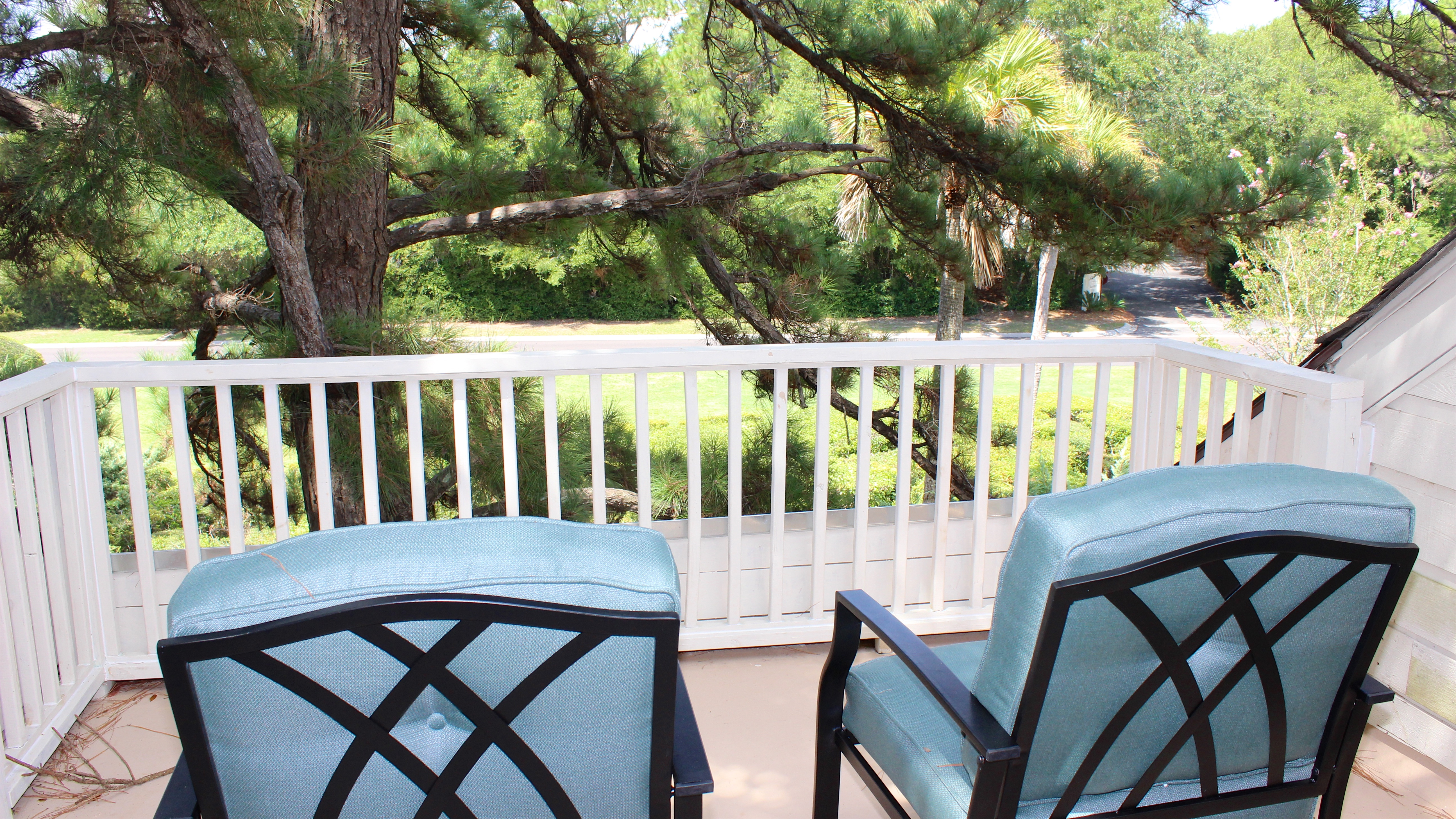 The sun deck is outfitted with cushioned chairs has a tranquil view.