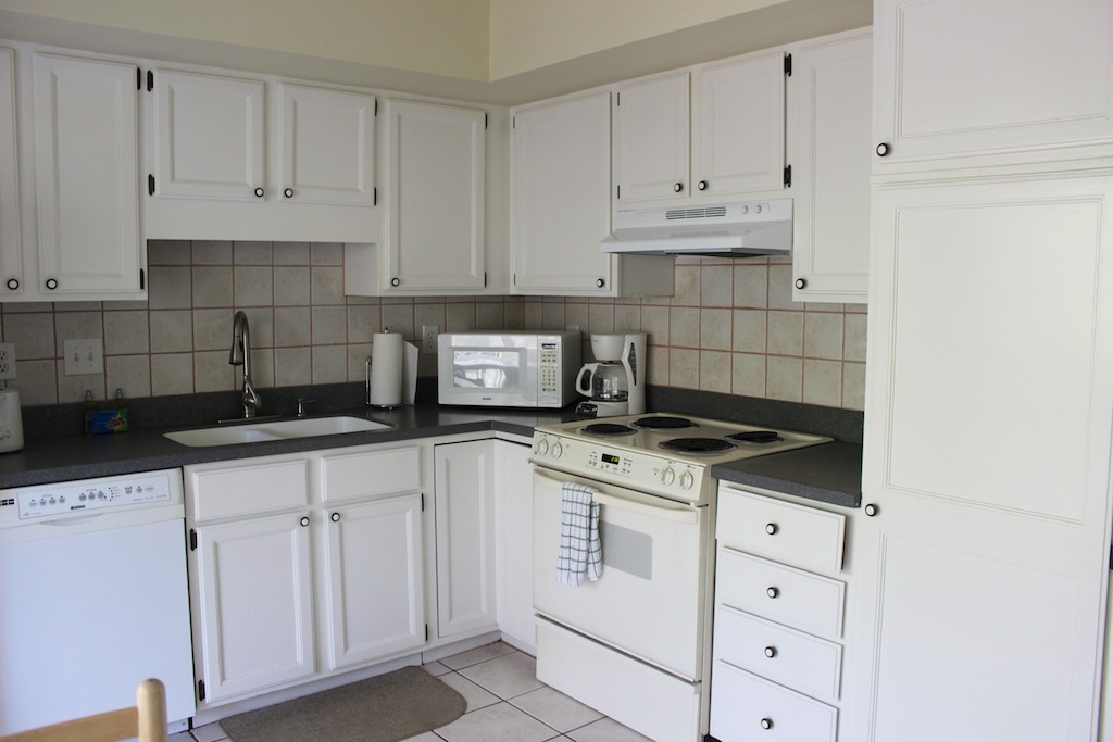 The kitchen has white cabinets, granite counters and a tile floor.
