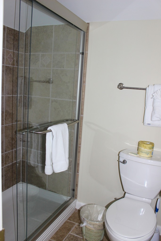 There is a large tiled shower in a separate room.