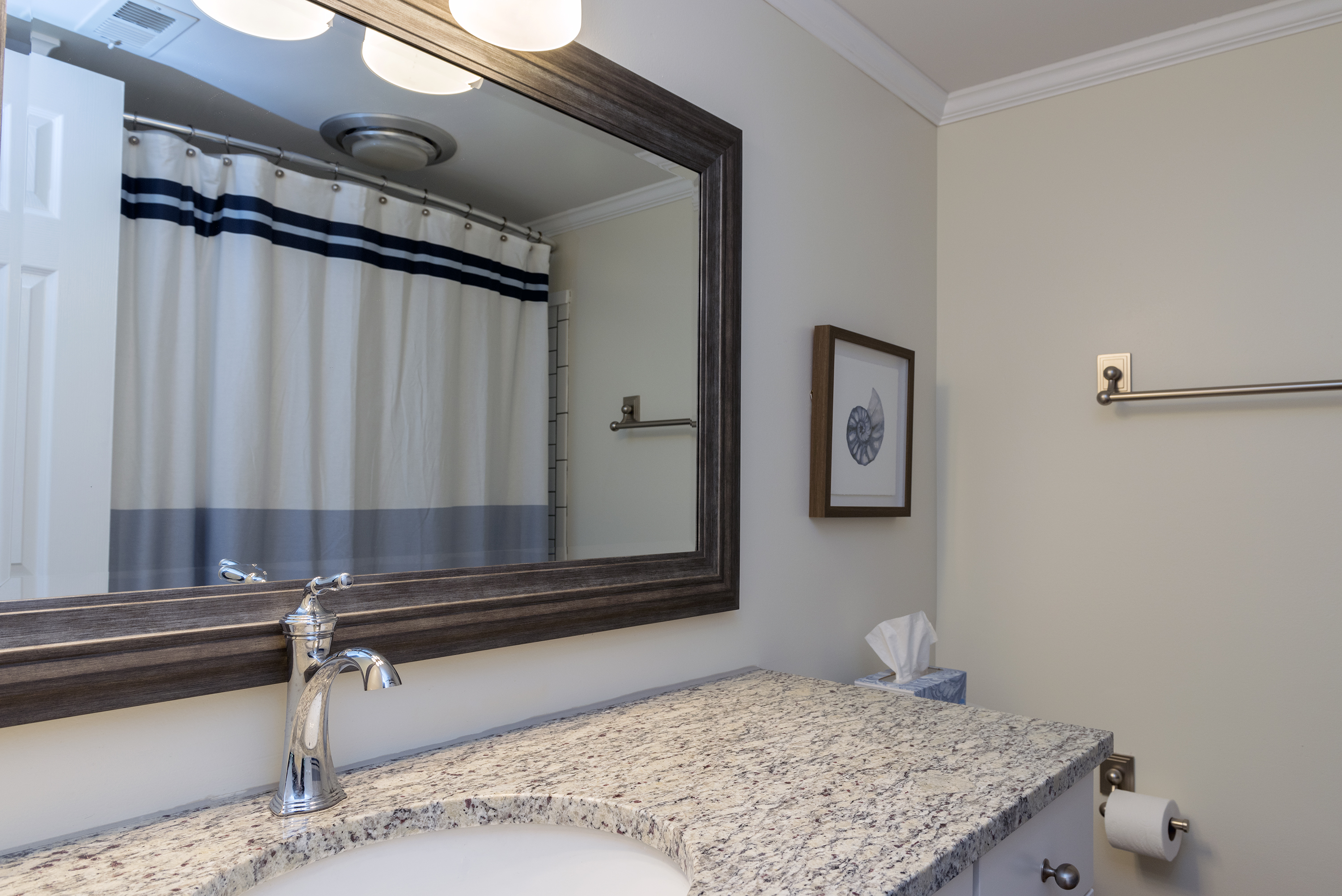 The hall bath is adjacent to the guest bedroom.  It has been renovated with granite counters and has a tiled tub/shower combo.