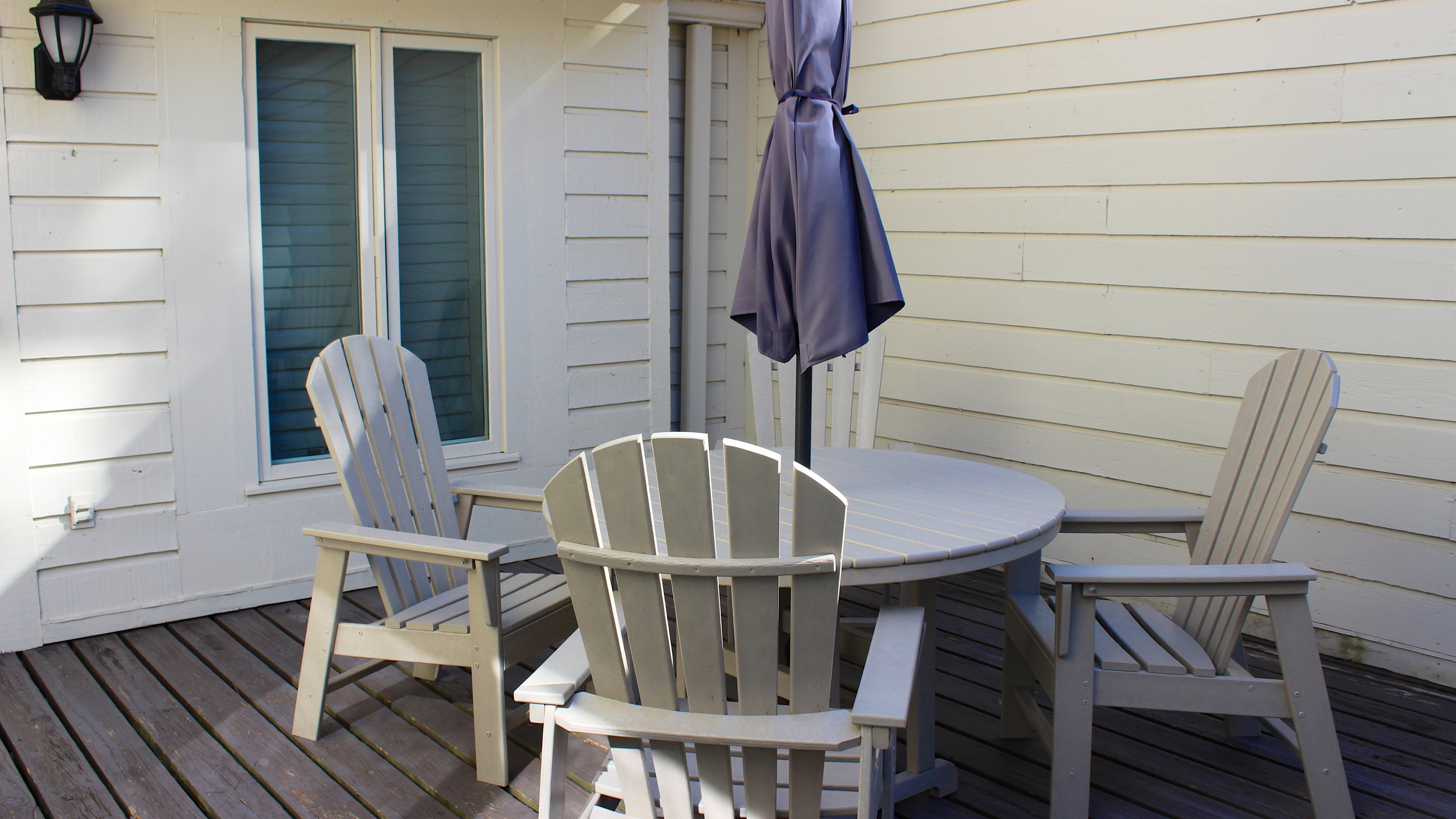 The entry porch has a table under the treed landscaping.