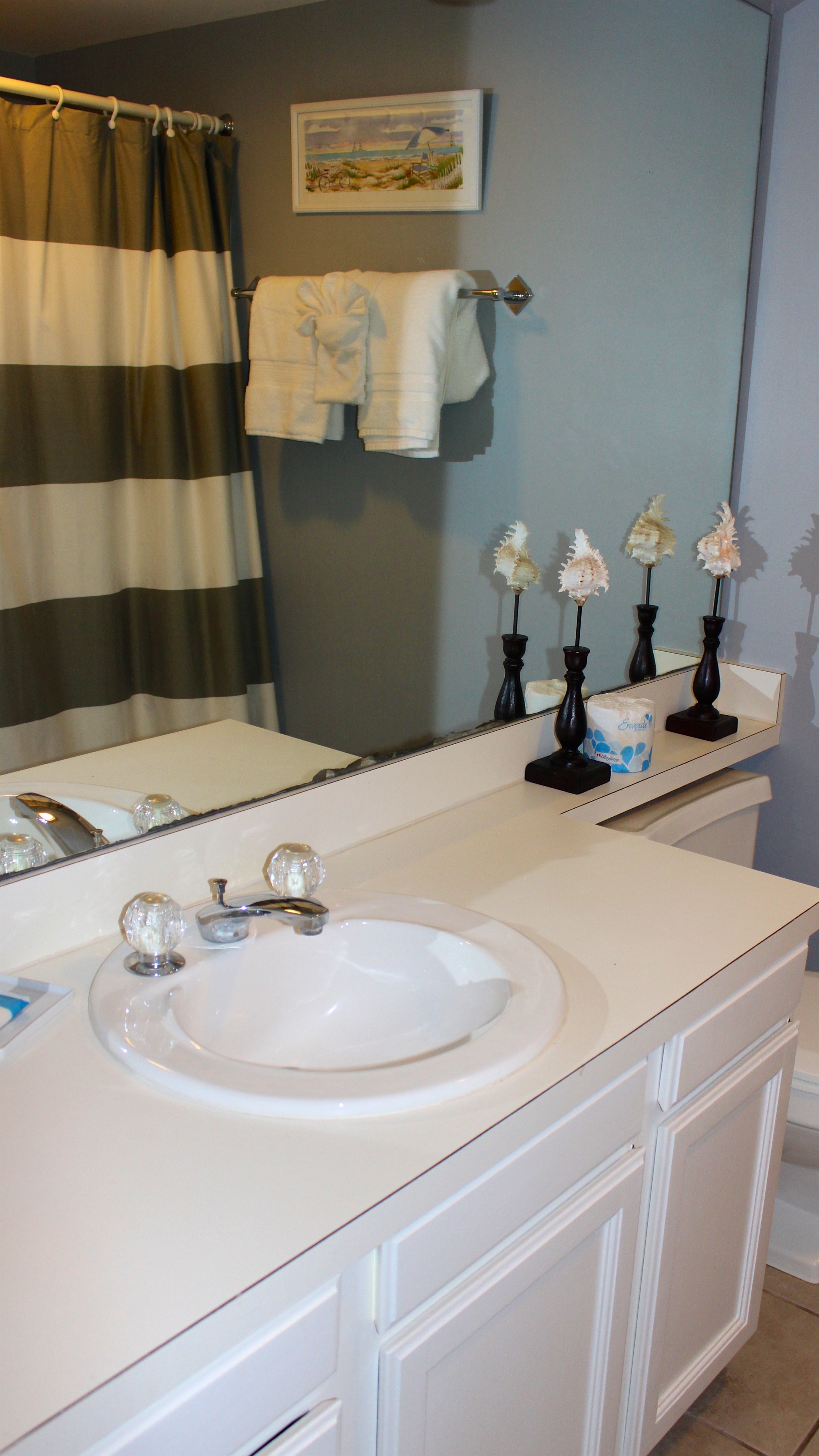 The hall bath has tile flooring, wide vanity and shower/tub.