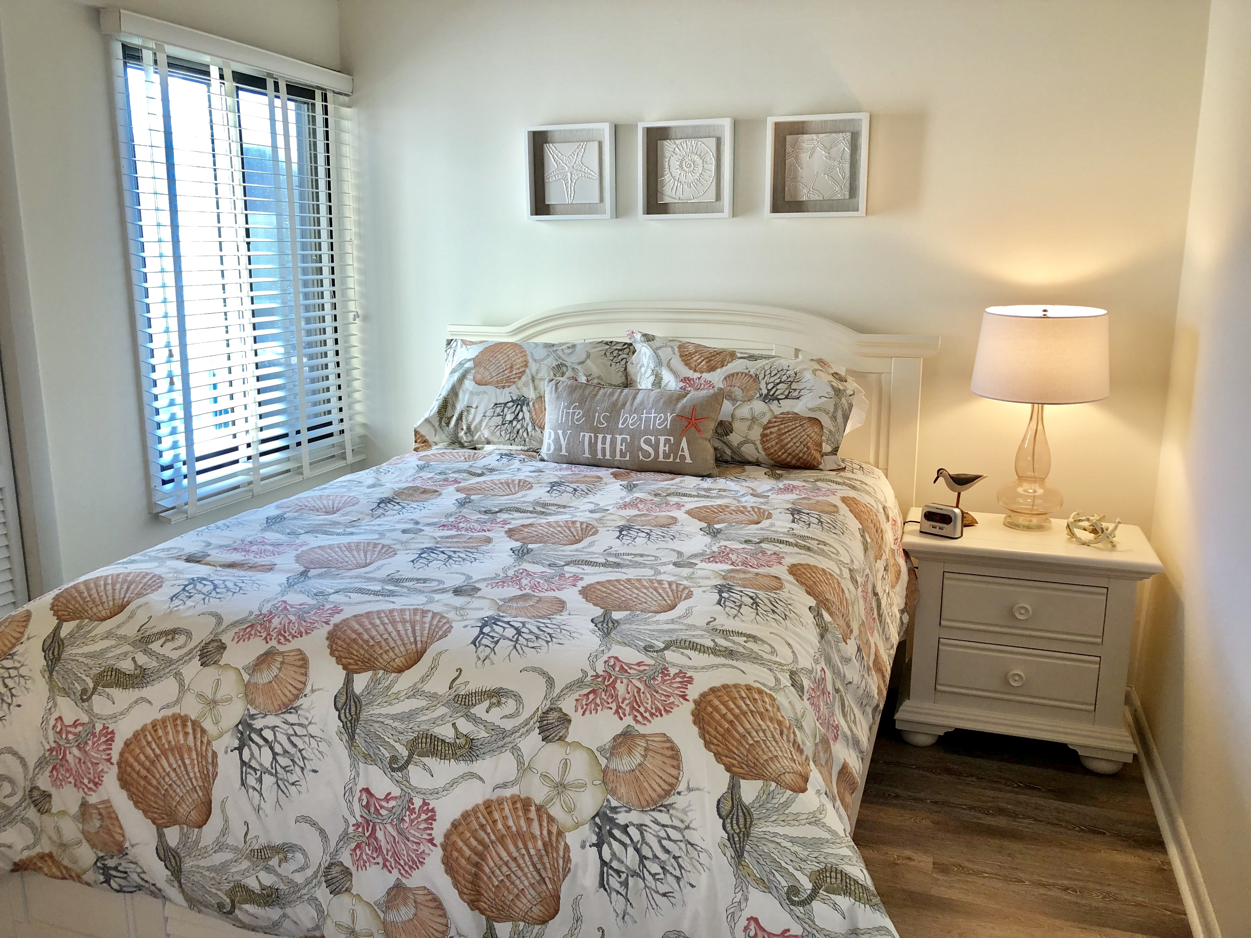 The guest bedroom has a queen size bed and lively seaside decor.