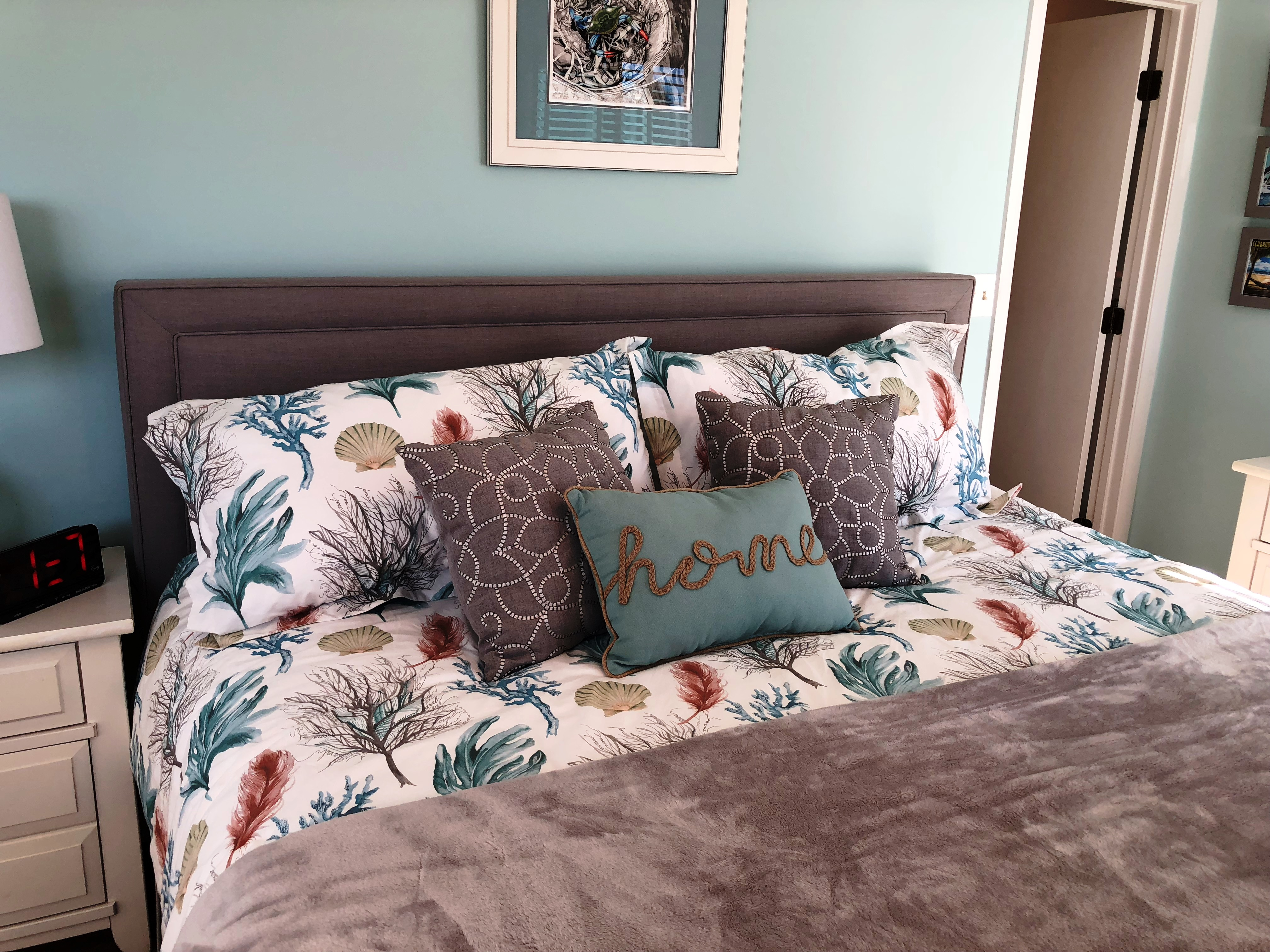 The master bedroom has a king size bed and pretty seaside decor.