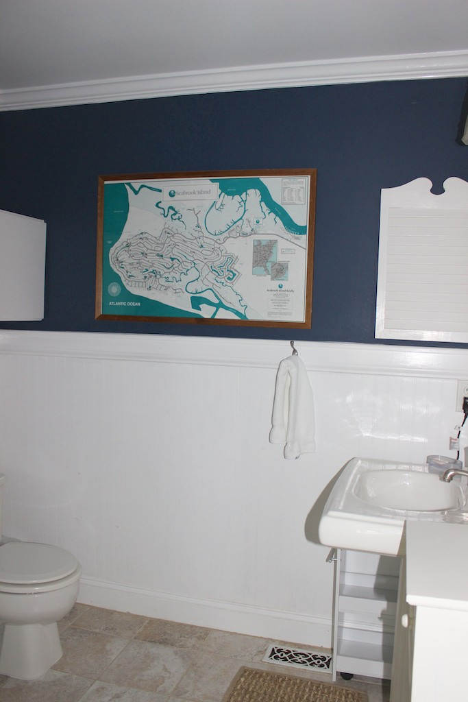 The master bath has wainscot, a pedestal sink and tile flooring.