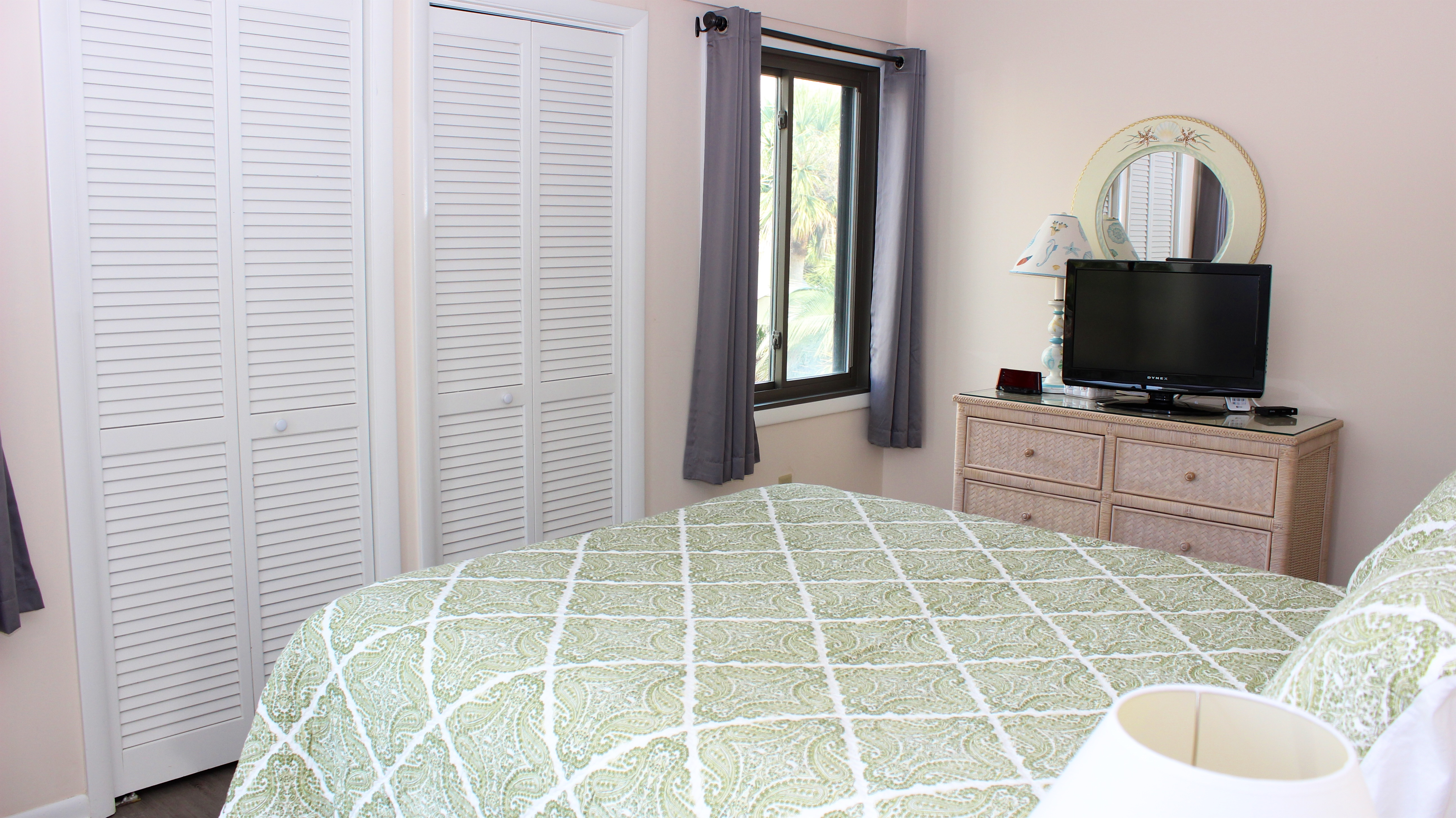 The master bedroom has a queen bed and flat screen TV.