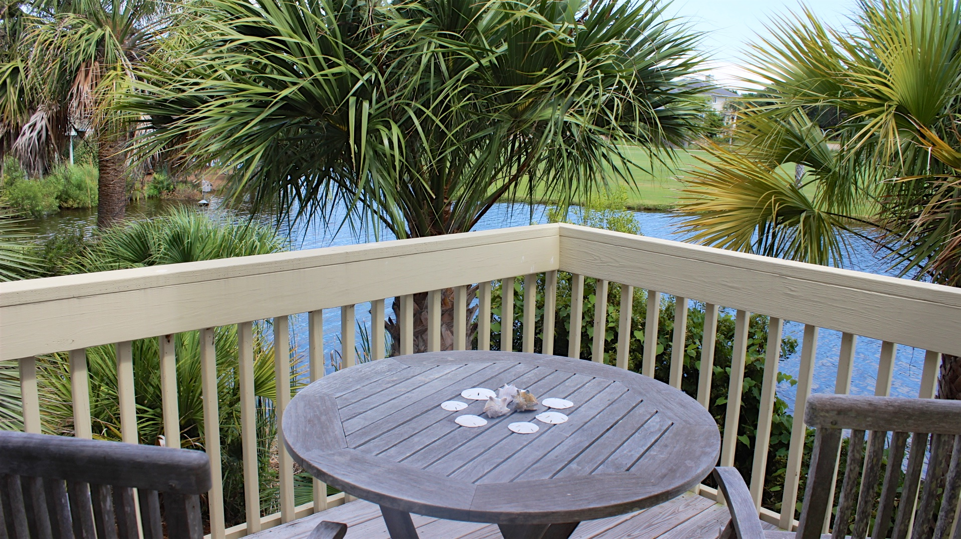 The deck off the master bedroom has lagoon views and is surrounded by palm trees.
