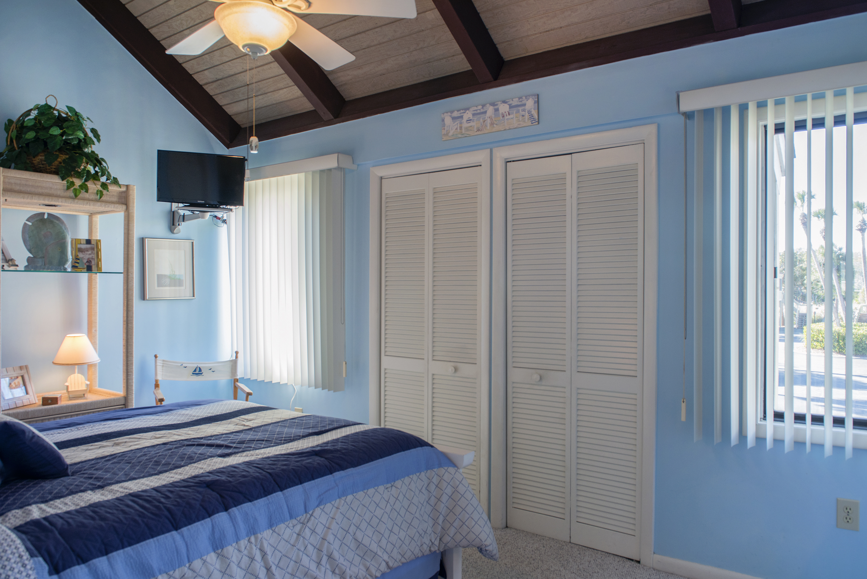 A wall mounted TV and plenty of closet space are in this bedroom.