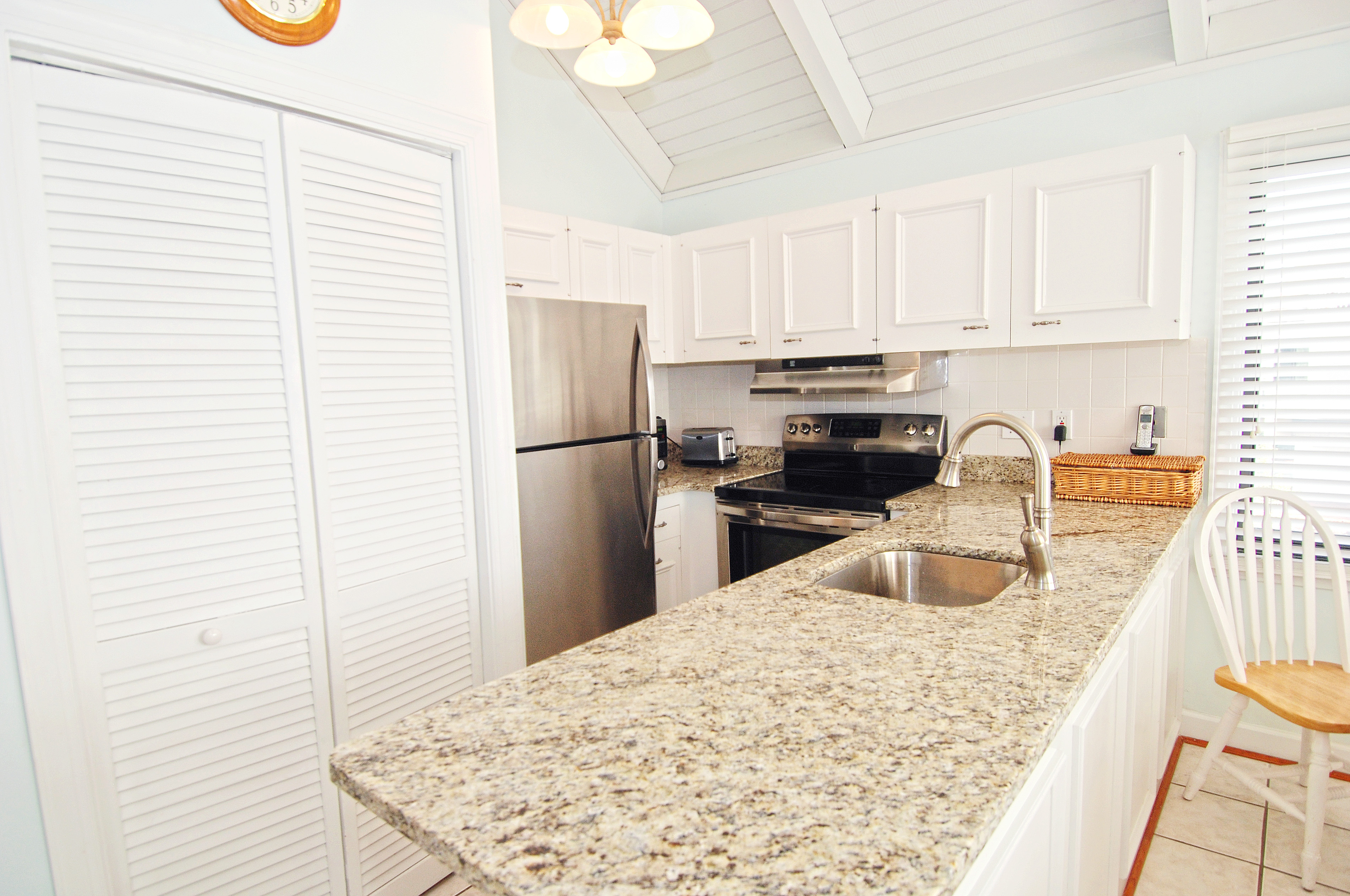 Granite counter tops, stainless steel appliances, and a washer/dryer closet are part of this remodeled kitchen.