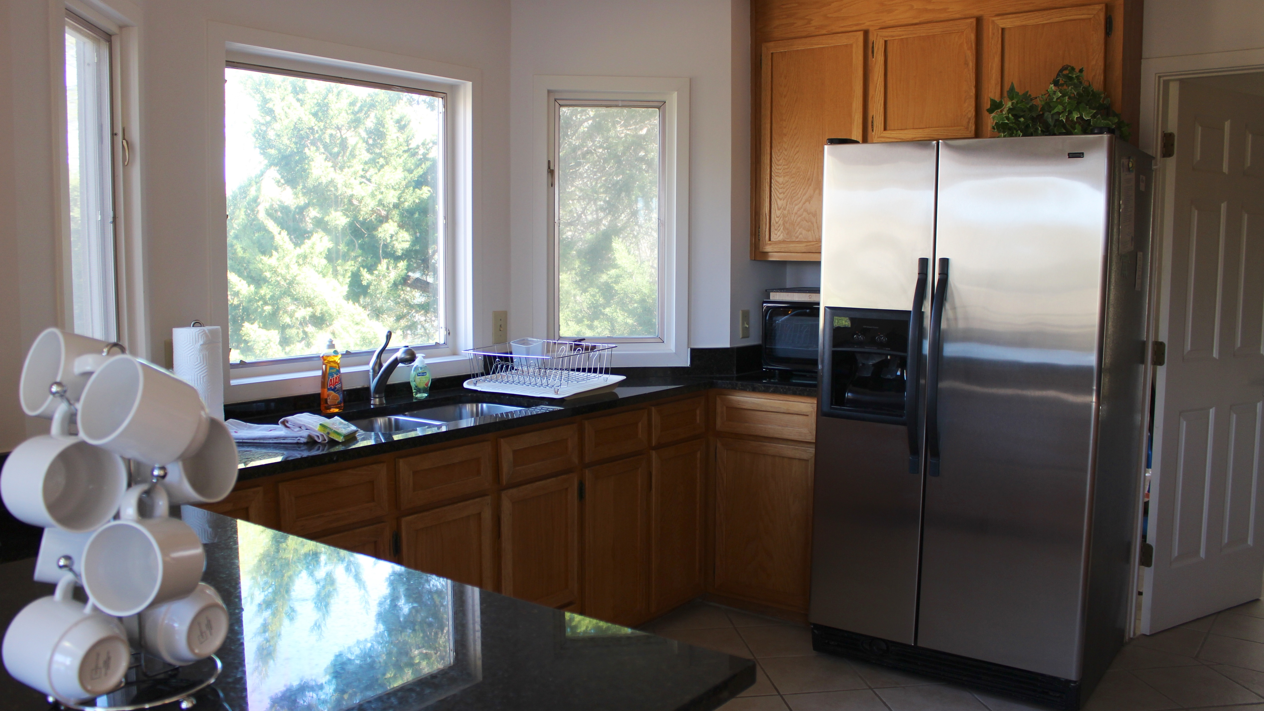 The kitchen features granite counters, tile flooring and great views.