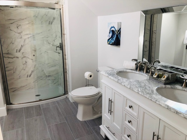 The large bathroom has a large walk-in shower and high ceilings.