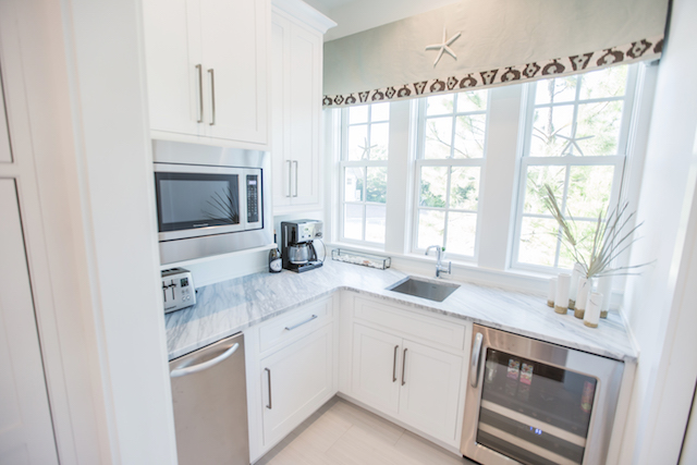 Butlers pantry off of kitchen with sink, wine refrigerator, microwave and very large walk-in pantry
