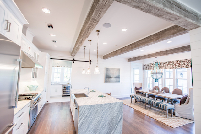 Kitchen overlooking the dining area and wall of windows overlooking pool