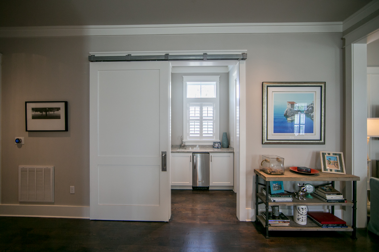 Large barn door encloses two pantry spaces and a wet bar and ice machine off to the side of the kitchen