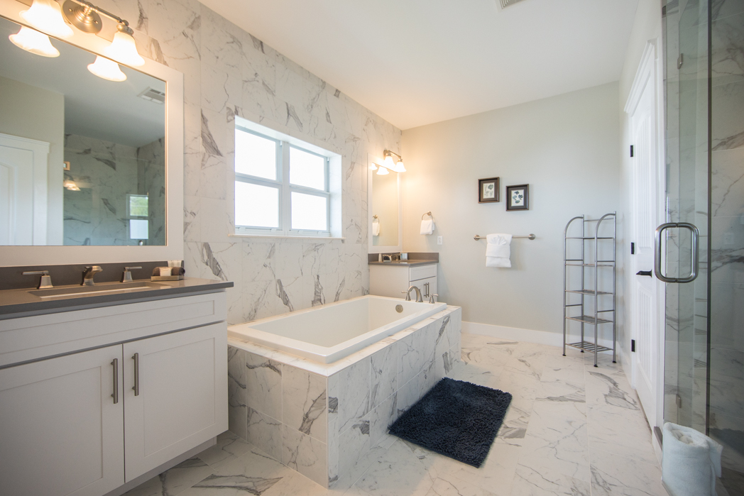 Master Bath with luxurious soaker tub, separate shower and white marble finishes
