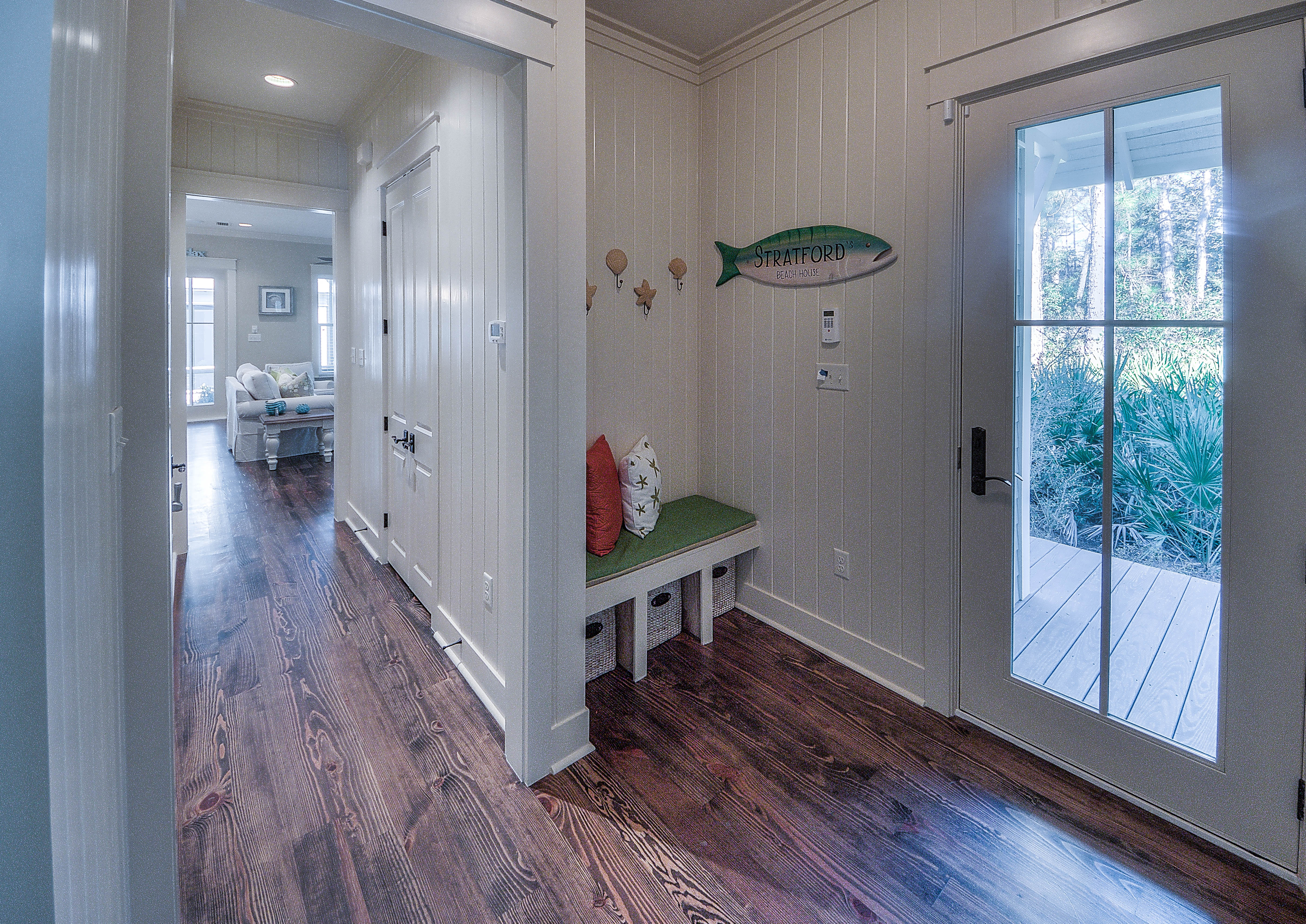 Entryway off of side of house with garage access door, first floor king master bedroom (at front of house) and hallway with powder and laundry room