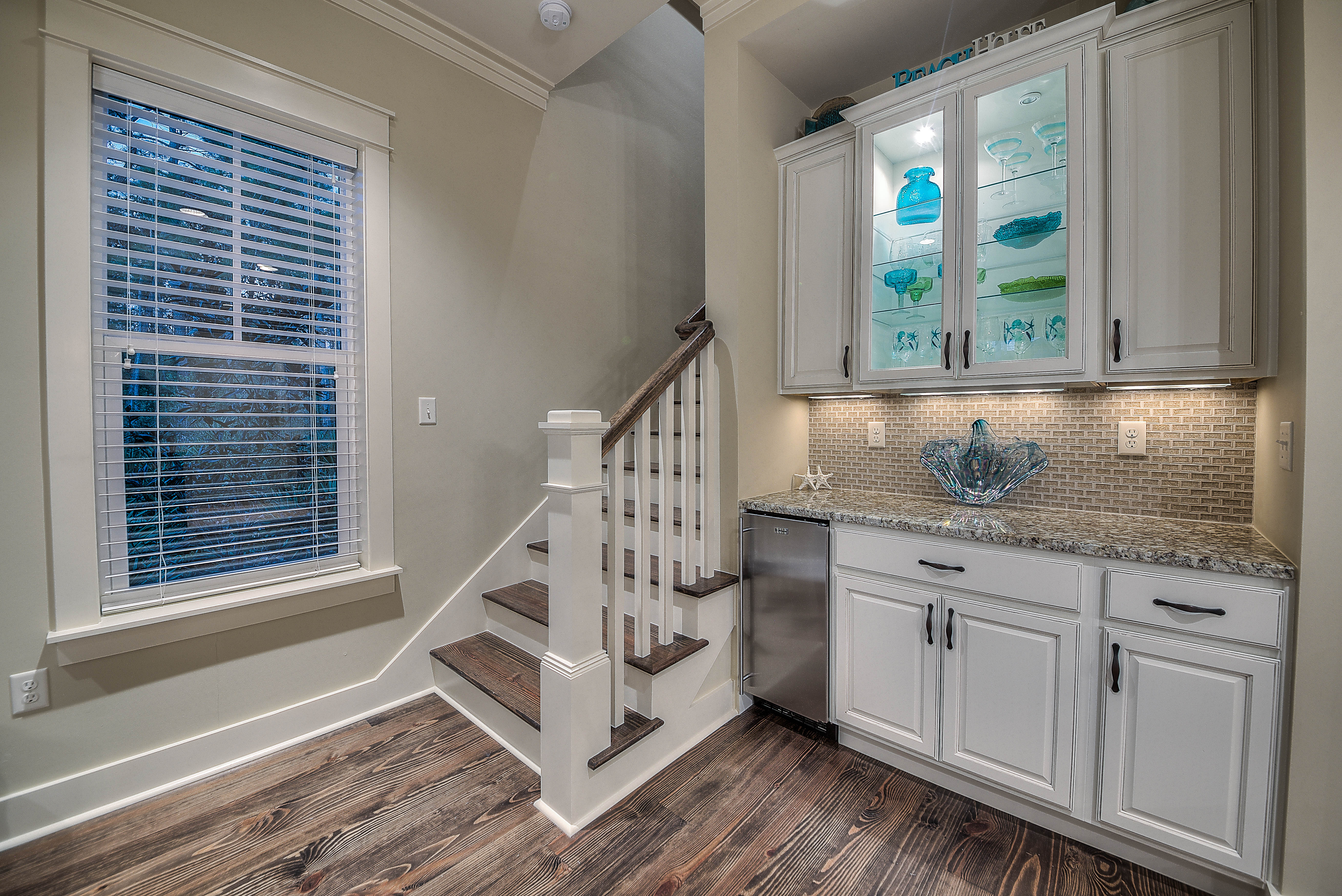First floor wet bar with ice maker adjacent to the kitchen and living room