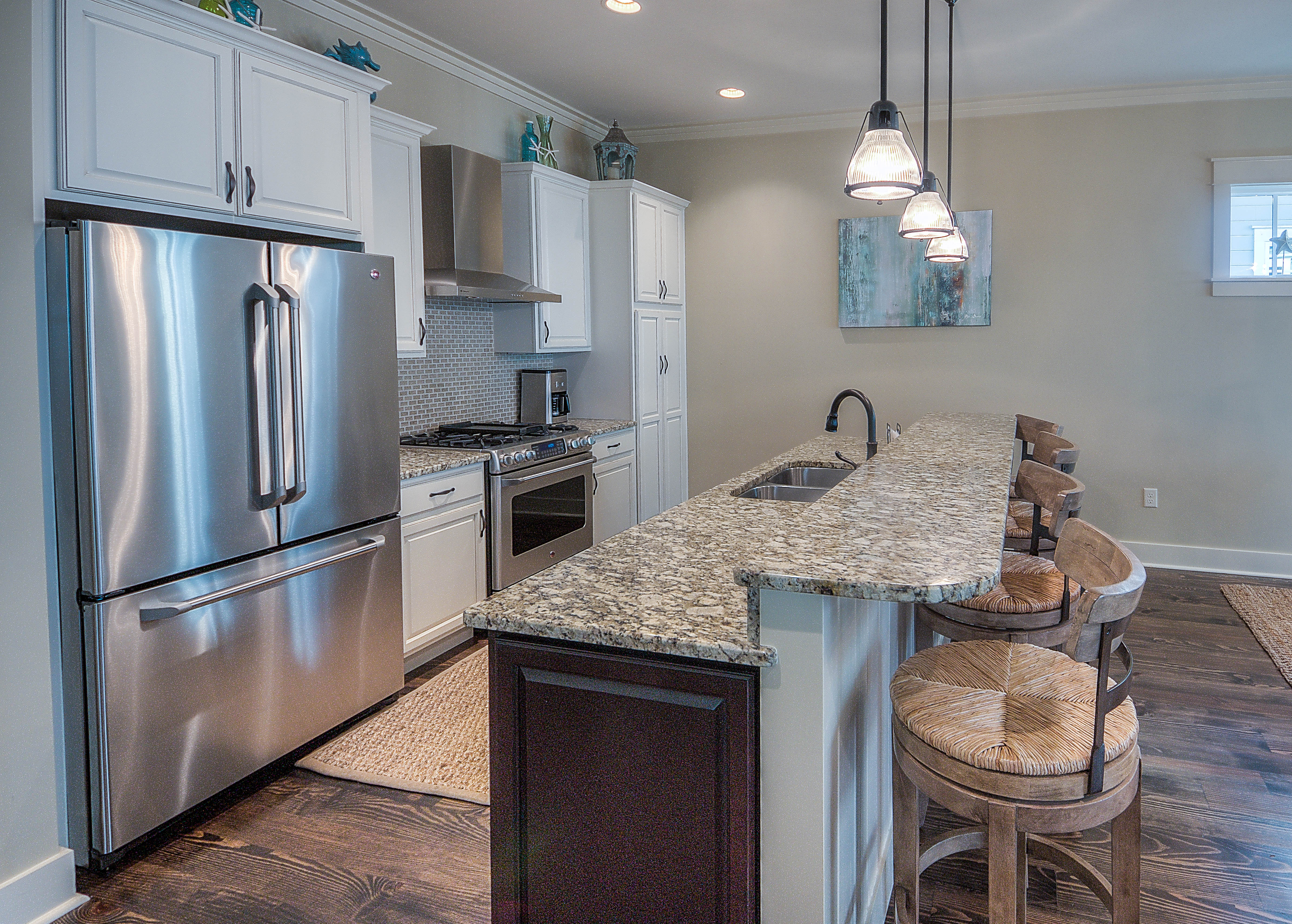 Open kitchen with stainless steel appliances, granite countertops and gas range
