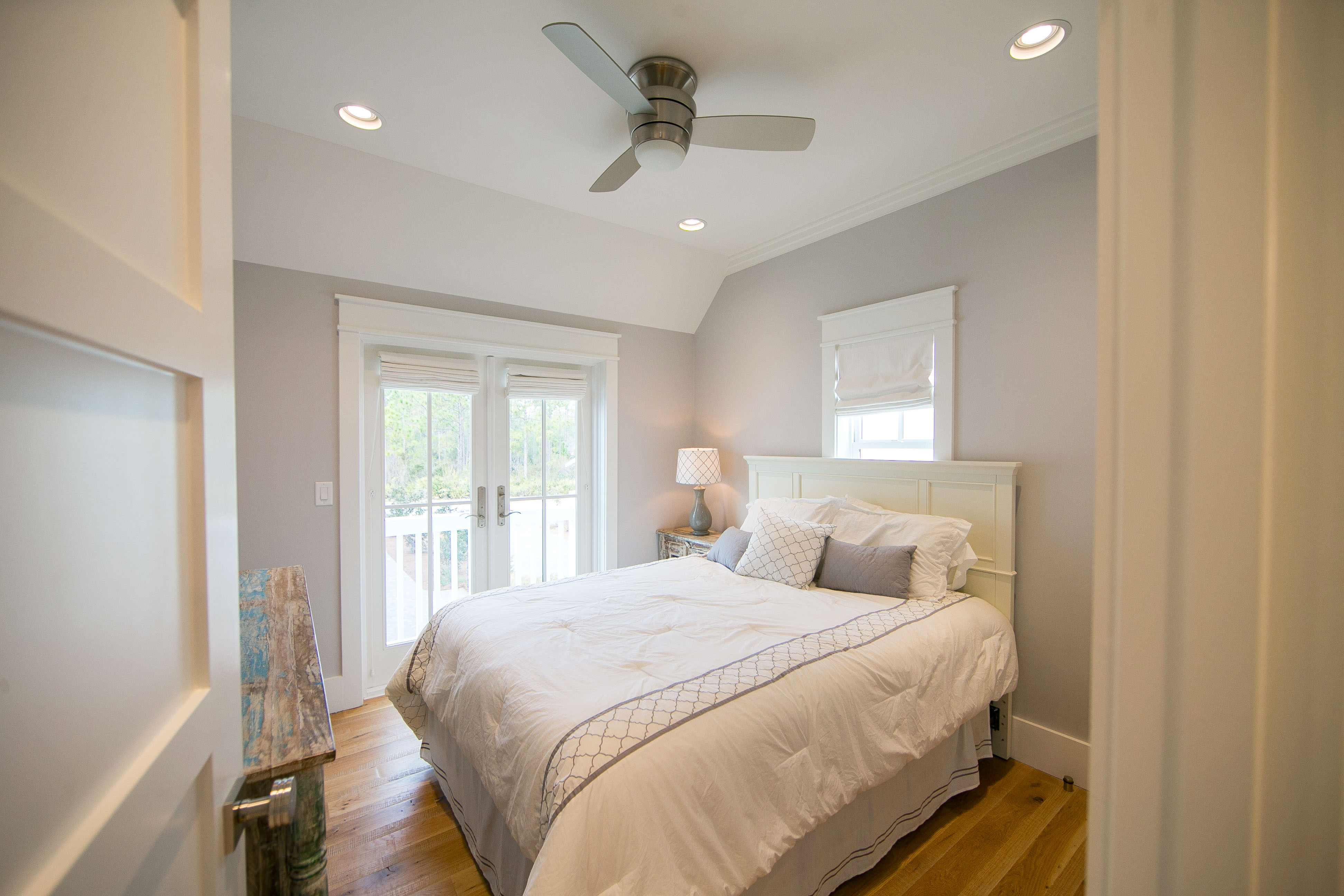 The carriage house bedroom has a queen sized bed and views of the pool.