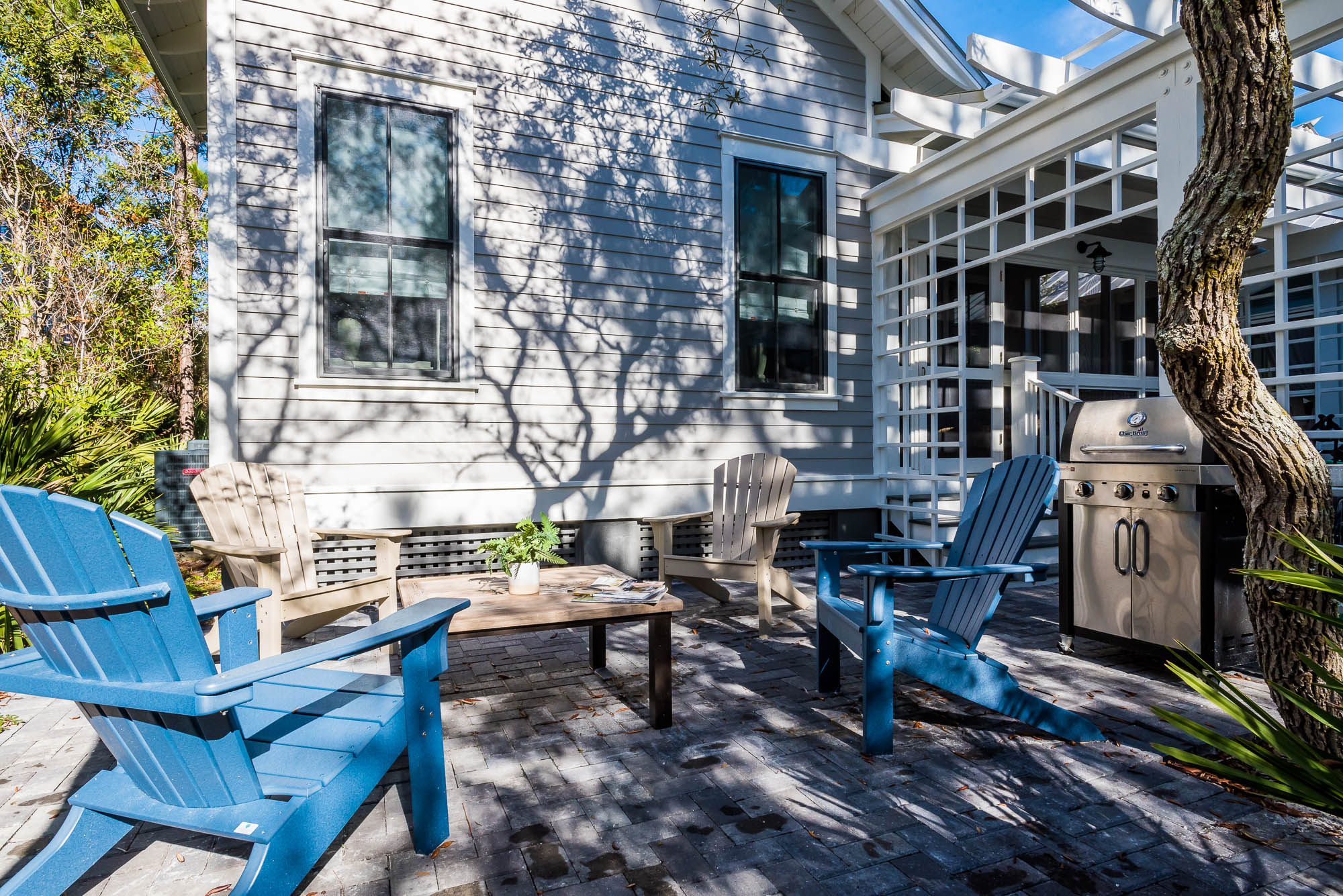 Lovely back patio with adirondack chairs and a grill