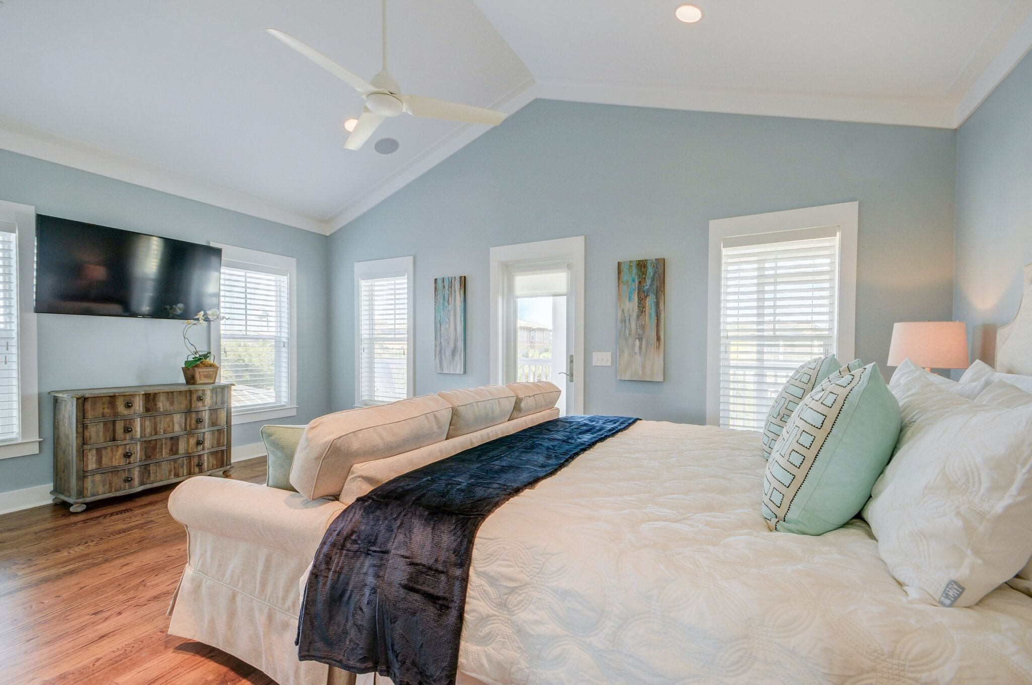 55 inch flat screen TV and couch offer private getaway space from the rest of the household in this large master suite