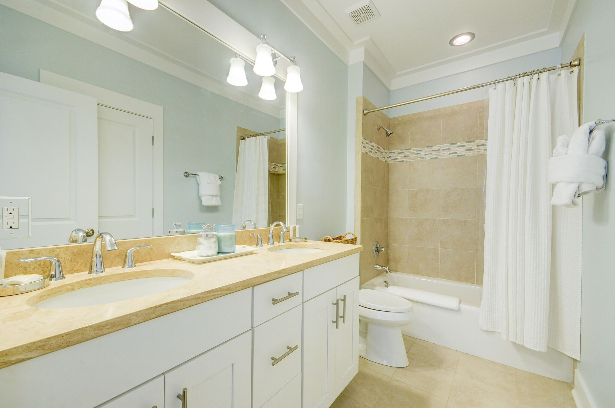 Shared 1st Floor Bathroom with Dual Vanities and shower/bath tub combo