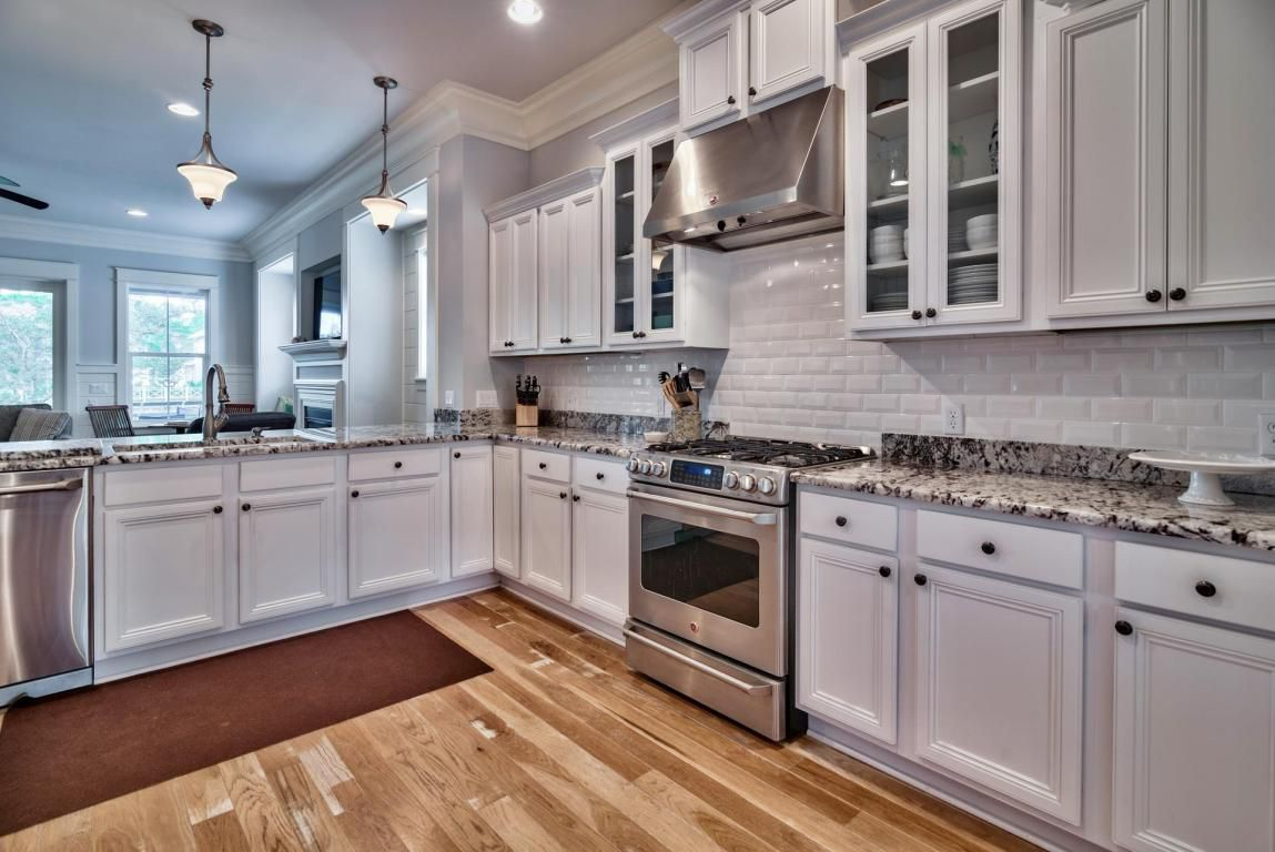 Grand gourmet chef's kitchen area with white cabinetry and spacious countertops